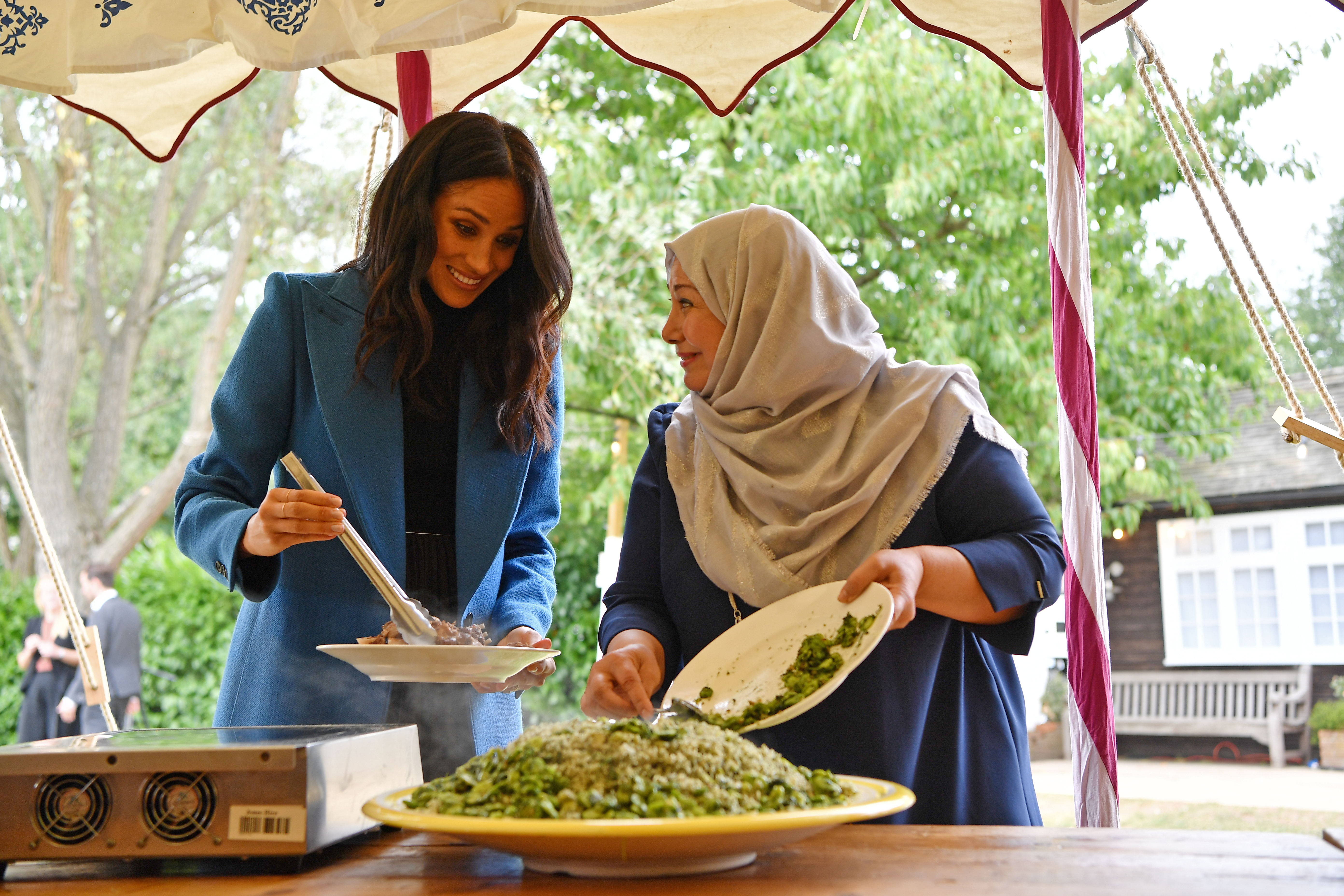 Meghan, Duchess of Sussex helps to prepare food at an event to mark the launch of a cookbook with recipes from a group of women affected by the Grenfell Tower fire at Kensington Palace on September 20, 2018 in London, England.