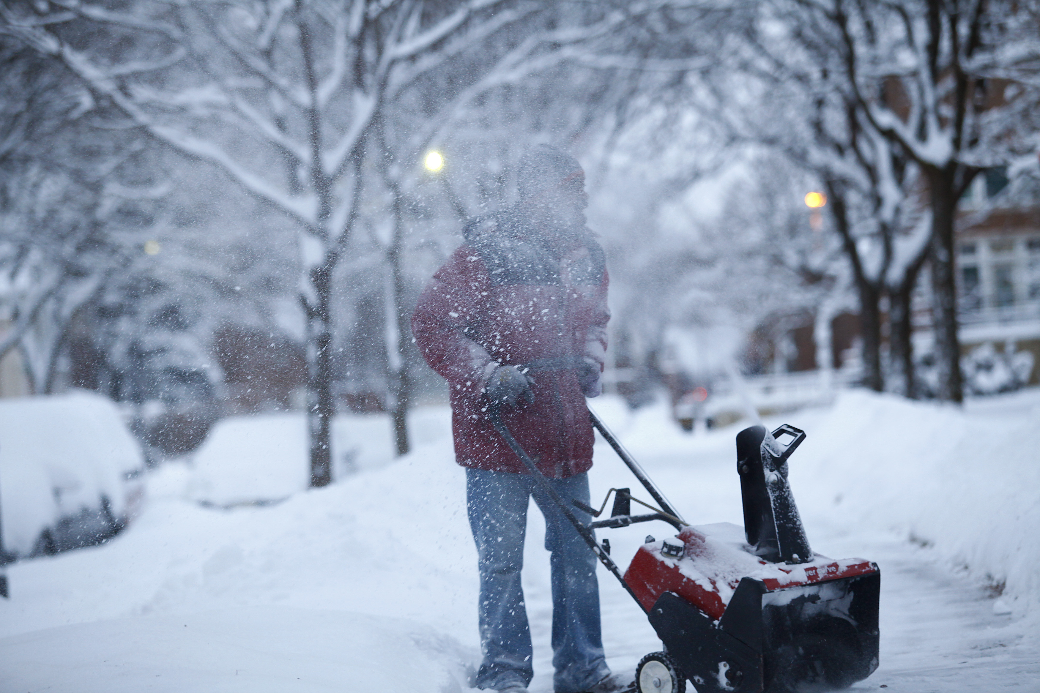 Larry Thomas snow blows several inches of snow from a sidewalk as the area deals with record breaking freezing weather January 6, 2014 in Detroit, Michigan. (Getty Images)