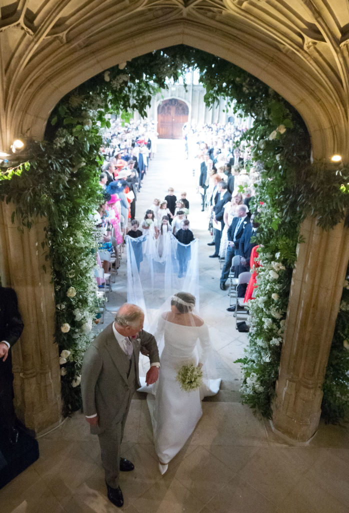 Meghan Markle walks up the aisle with the Prince Charles, Prince of Wales at St George's Chapel at Windsor Castle during her wedding to Prince Harry on May 19, 2018 in Windsor, England.. (Photo by Dominic Lipinski/ - WPA Pool/Getty Images)