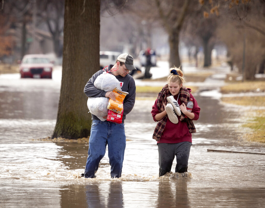 Anthony Thomson, left, and Melody Walton make their way out of a flooded neighborhood Sunday, March 17, 2019, in Fremont, Neb. (AP)