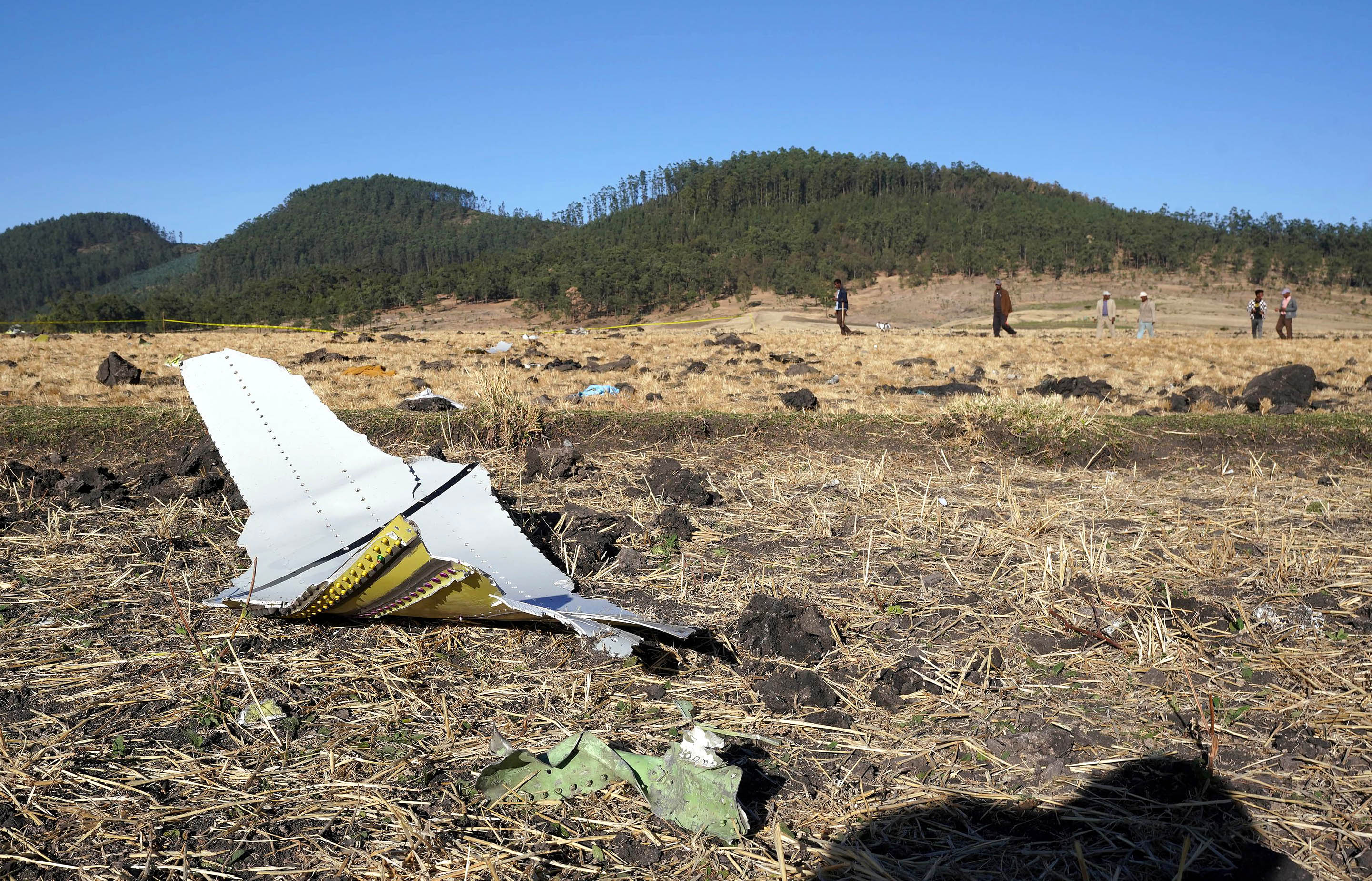 A piece of the fuselage of ET Flight 302 can be seen in the foreground as local residents collect debris at the scene where Ethiopian Airlines Flight 302 crashed in a wheat field just outside the town of Bishoftu, 62 kilometers southeast of Addis Ababa on March 10, 2019, in Addis Ababa, Ethiopia. (Getty)