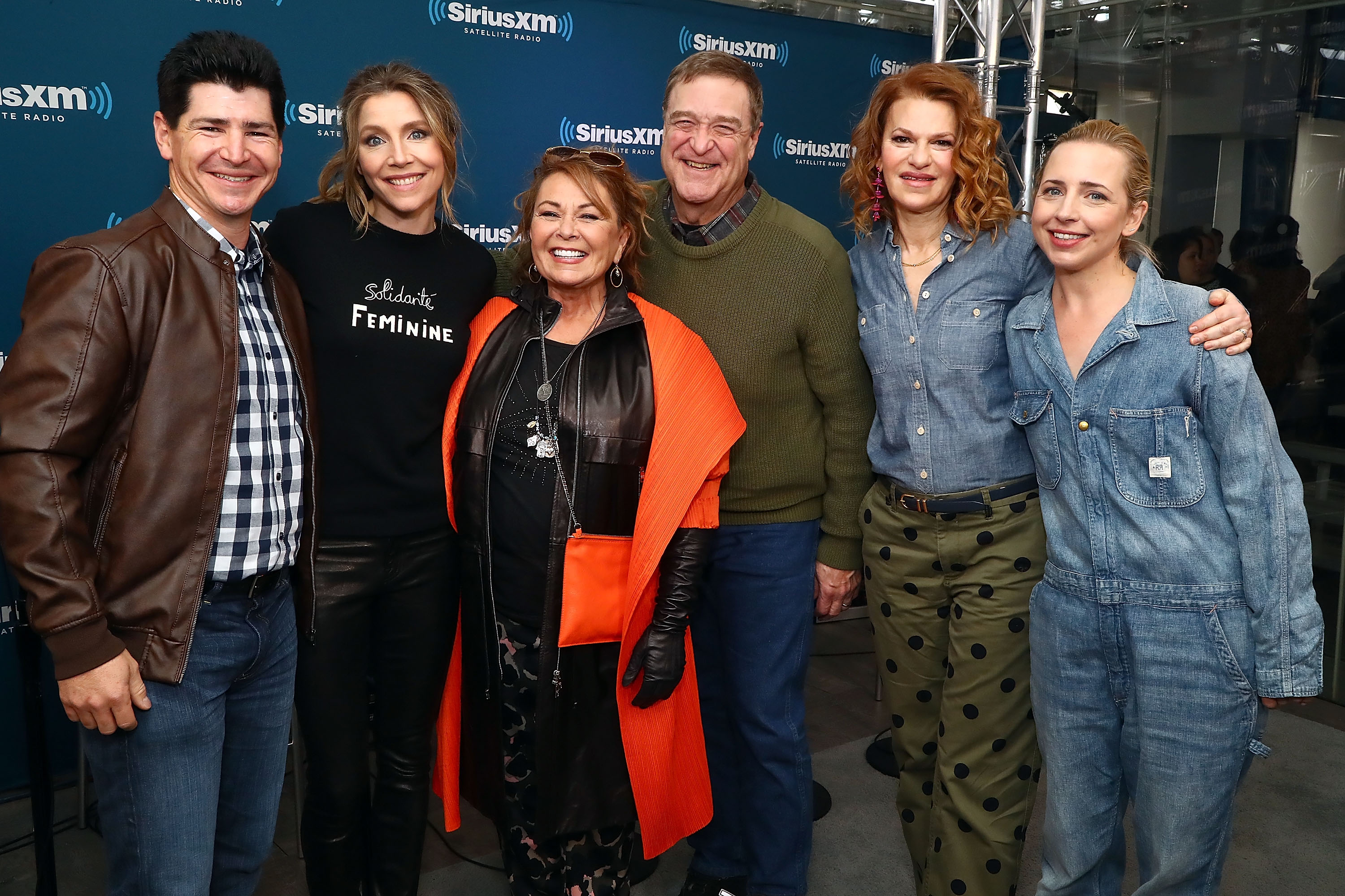 (L-R) Actors Michael Fishman, Sarah Chalke, Roseanne Barr, John Goodman, SiriusXM host Sandra Bernhard and Lecy Goranson pose for photos during SiriusXM's Town Hall with the cast of Roseanne on March 27, 2018 in New York City.