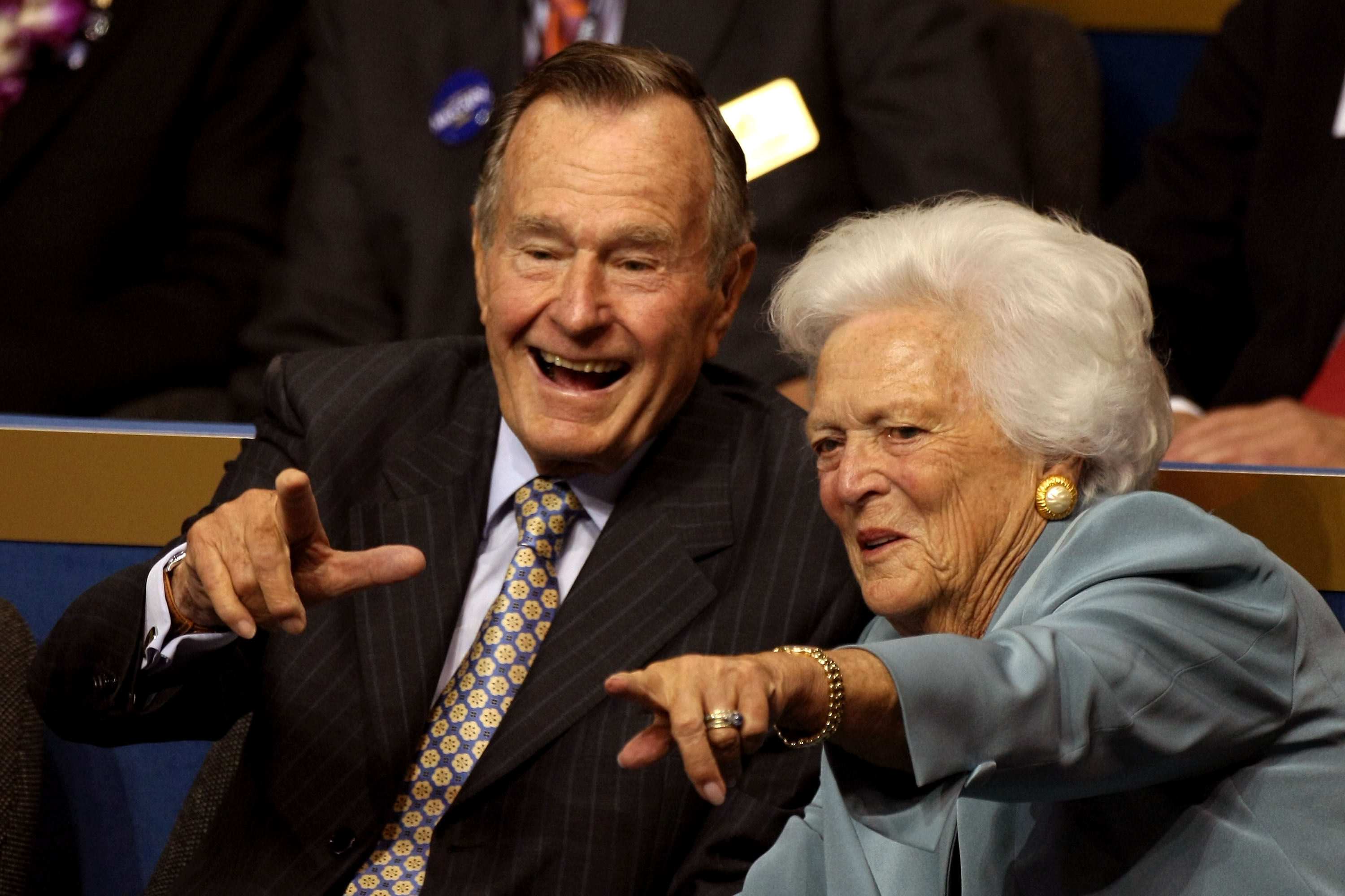 Former President George H.W. Bush (L) and former first lady Barbara Bush (C) point from their seats on day two of the Republican National Convention (RNC) at the Xcel Energy Center on September 2, 2008 in St. Paul, Minnesota.