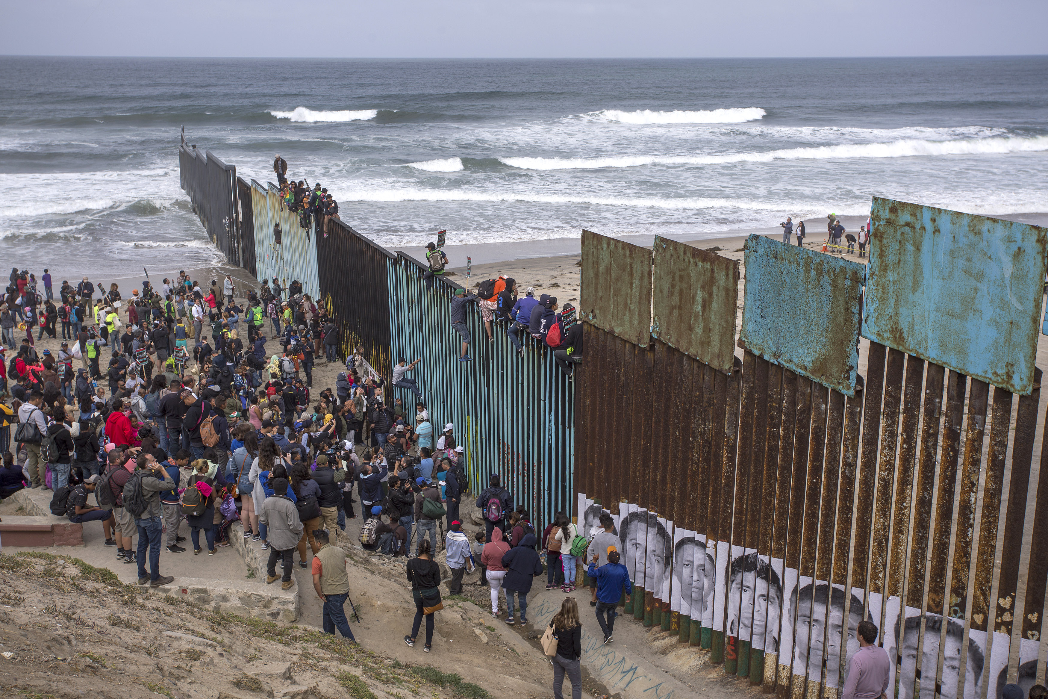 People climb a section of border fence to look into the U.S. as members of a caravan of Central American asylum seekers arrive to a rally on April 29, 2018 in Tijuana, Baja California Norte, Mexico.
