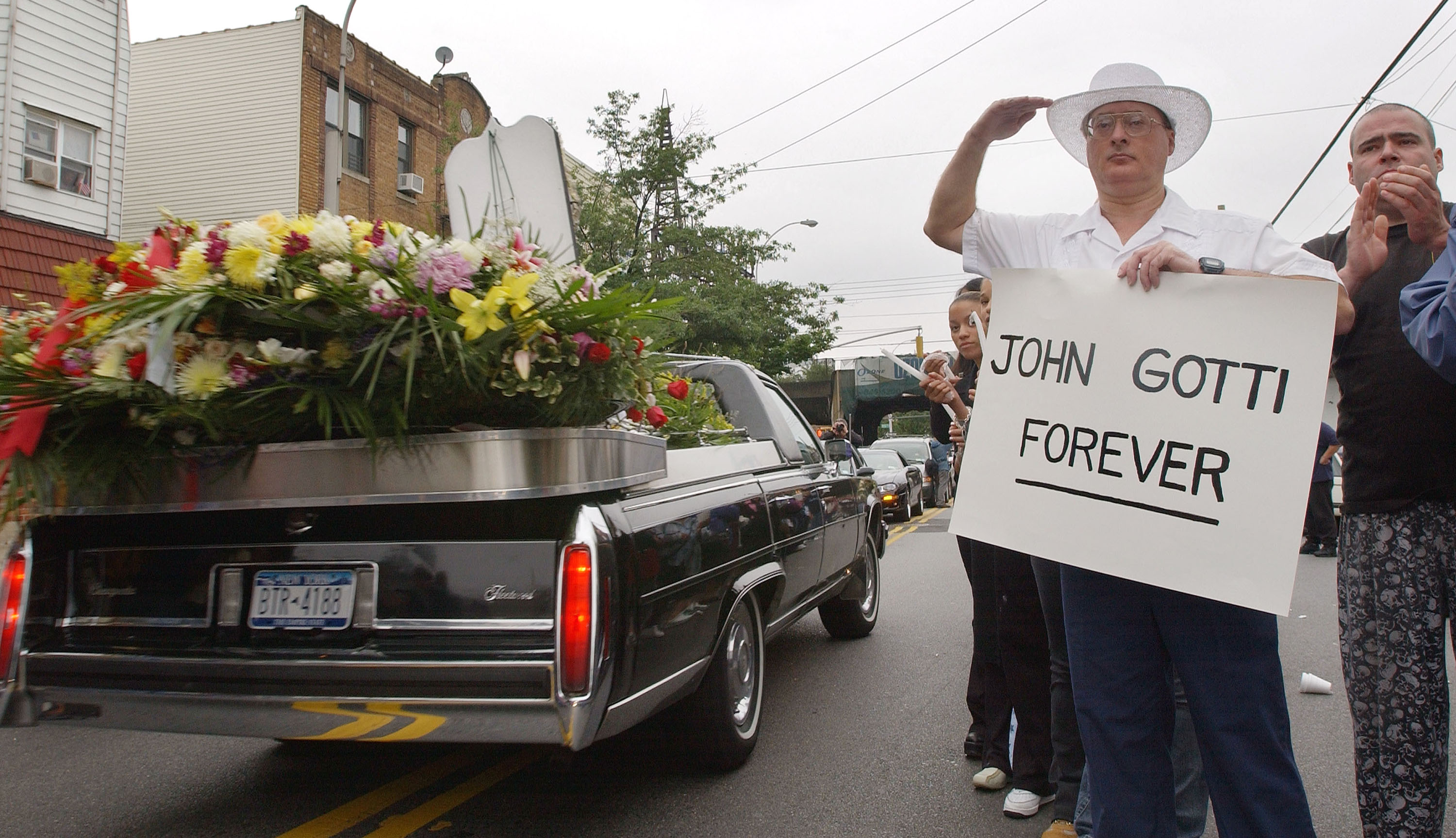 An admirer of legendary crime boss John Gotti salutes and holds a sign which reads,' John Gotti Forever' as Gotti's funeral procession passes by the Bergin Hunt and Fish Club June 15, 2002 in Queens, New York. Gotti, 61, died in a federal prison hospital June 10, 2002 from complications of head and neck cancer. Gotti was laid to rest at St. Johns Cemetery in Queens.