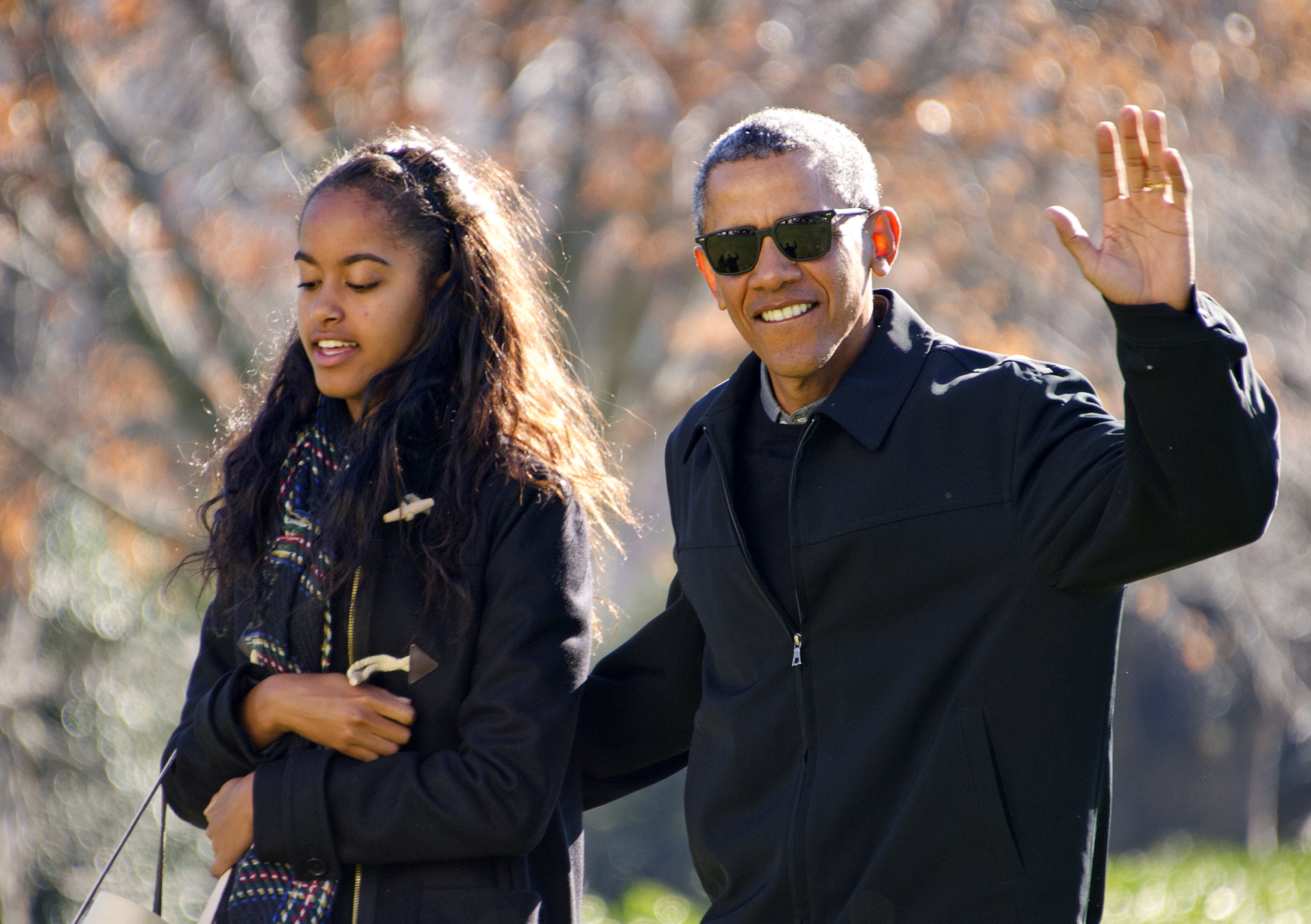 (AFP OUT) U.S. President Barack Obama waves to the assembled press as he walks with his daughter Malia on his family's return to the South Lawn of the White House January 3, 2016 in Washington, DC. The first family is returning from their two week Hawaiian vacation