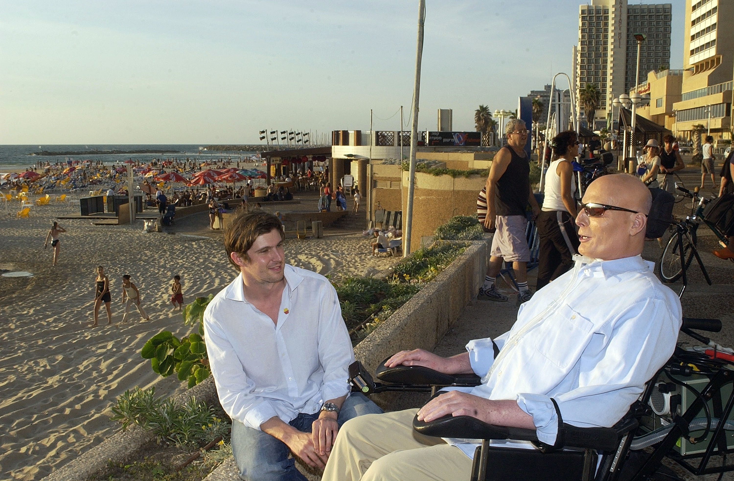Former actor Christopher Reeve and his son Matthew talk on the promenade overlooking the Mediterranean Sea on August 1, 2003, in Tel Aviv, Israel. (Getty)