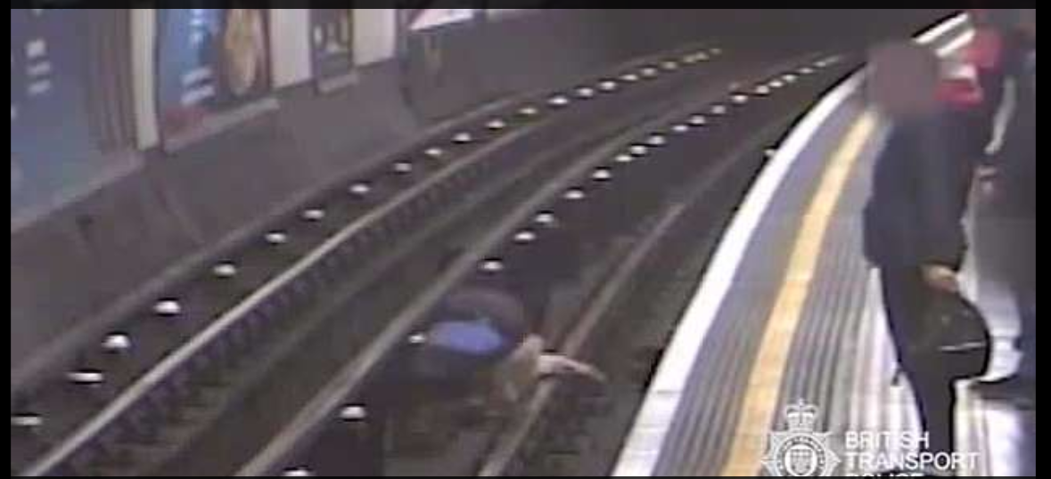 Sir Robert can be seen lying on the tracks as the Frenc teacher jumps down to help him.
