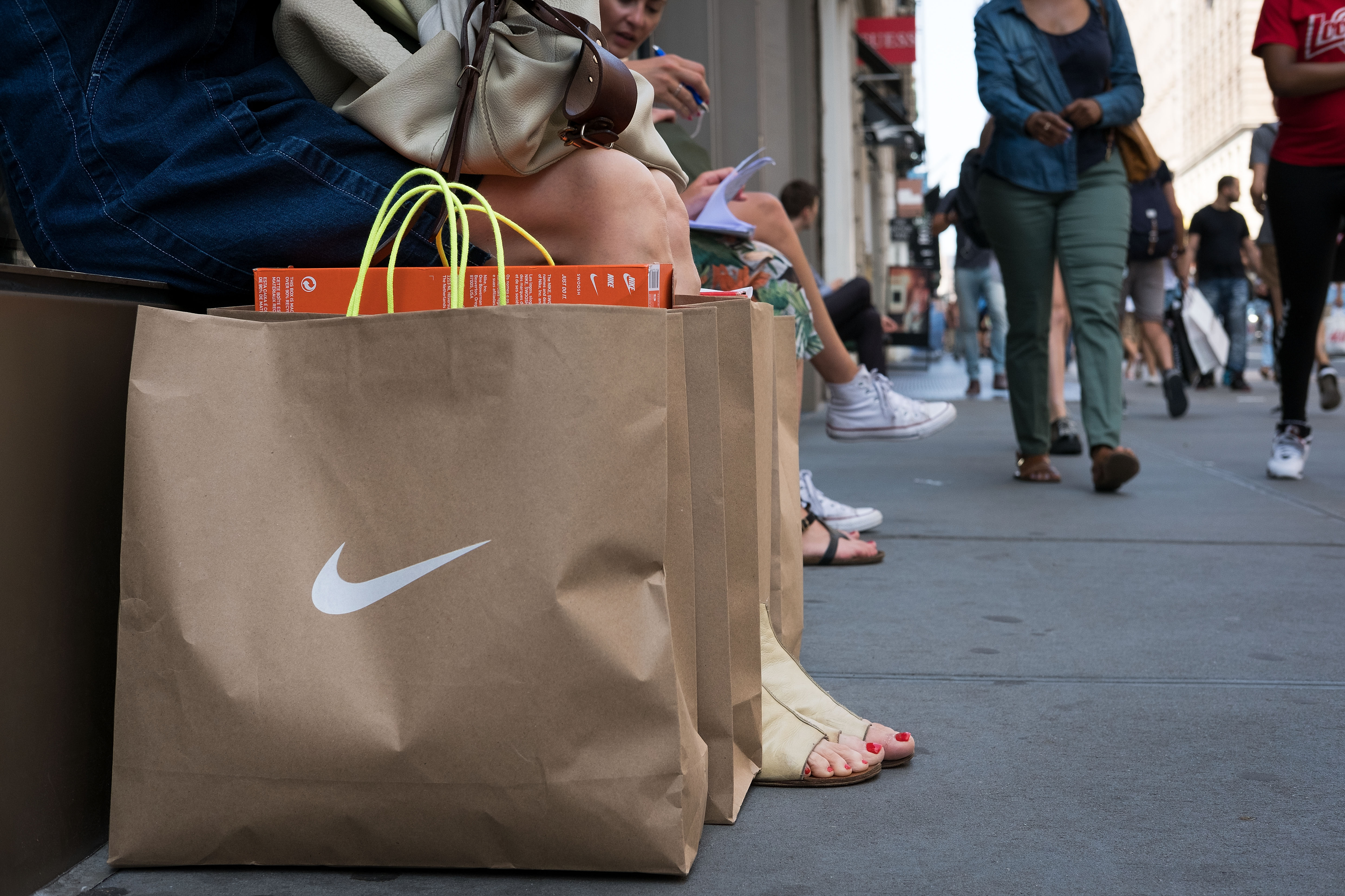 A shopper sits next to Nike shopping bags outside the Nike SoHo store, June 15, 2017, in New York City (Getty Images)