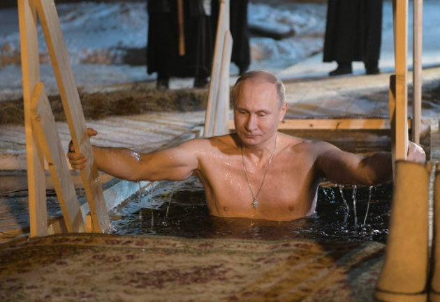 Russian President Vladimir Putin climbing out of icy waters. (Getty)