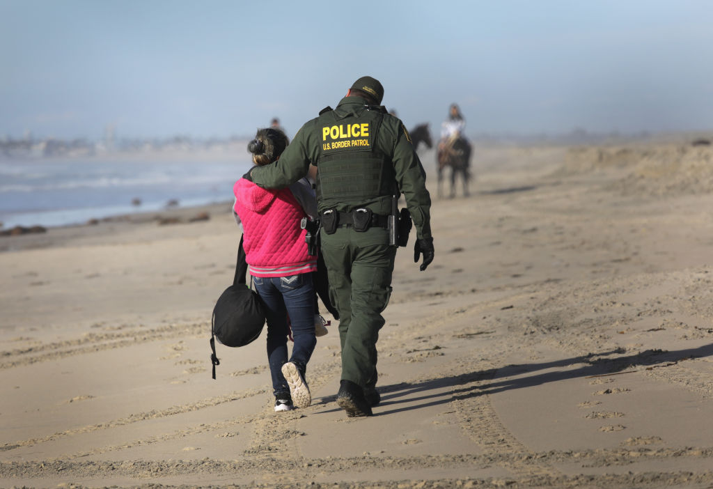 A US Border Patrol agent takes an immigrant into custody after she passed through a breach in the U.S.-Mexico border fence on the beach December 2, 2018, in Tijuana, Mexico. (Photo by John Moore/Getty Images)