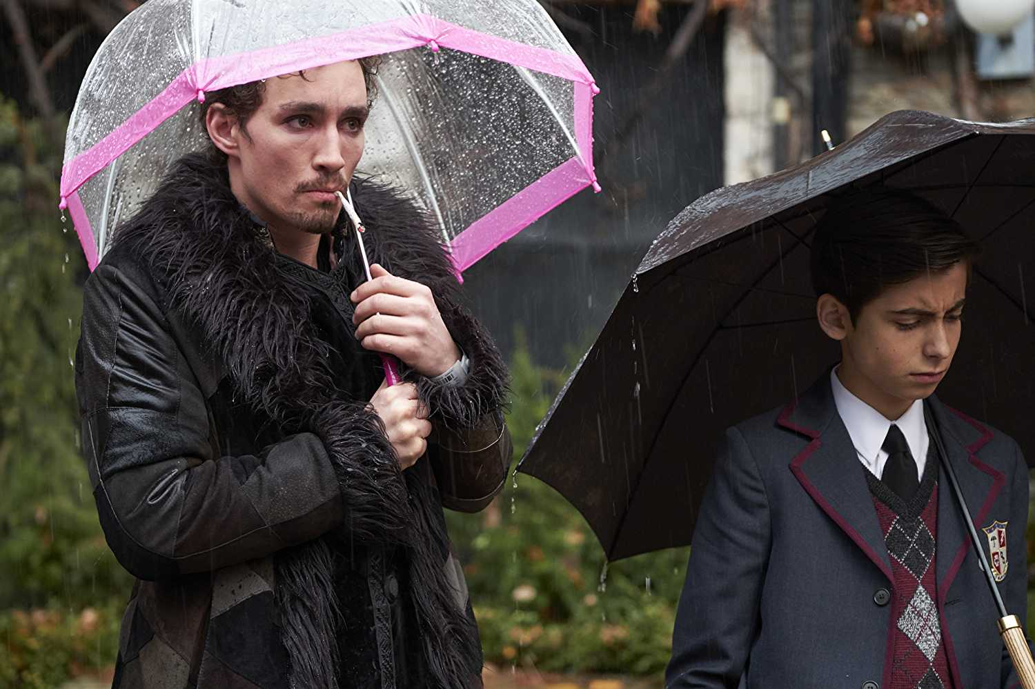 Best buds, Klaus Hargreeves (Robert Sheehan) and Number Five (Aidan Gallagher) mourning the death of their adoptive father, Sir Reginald Hargreeves. (Source: IMDB)
