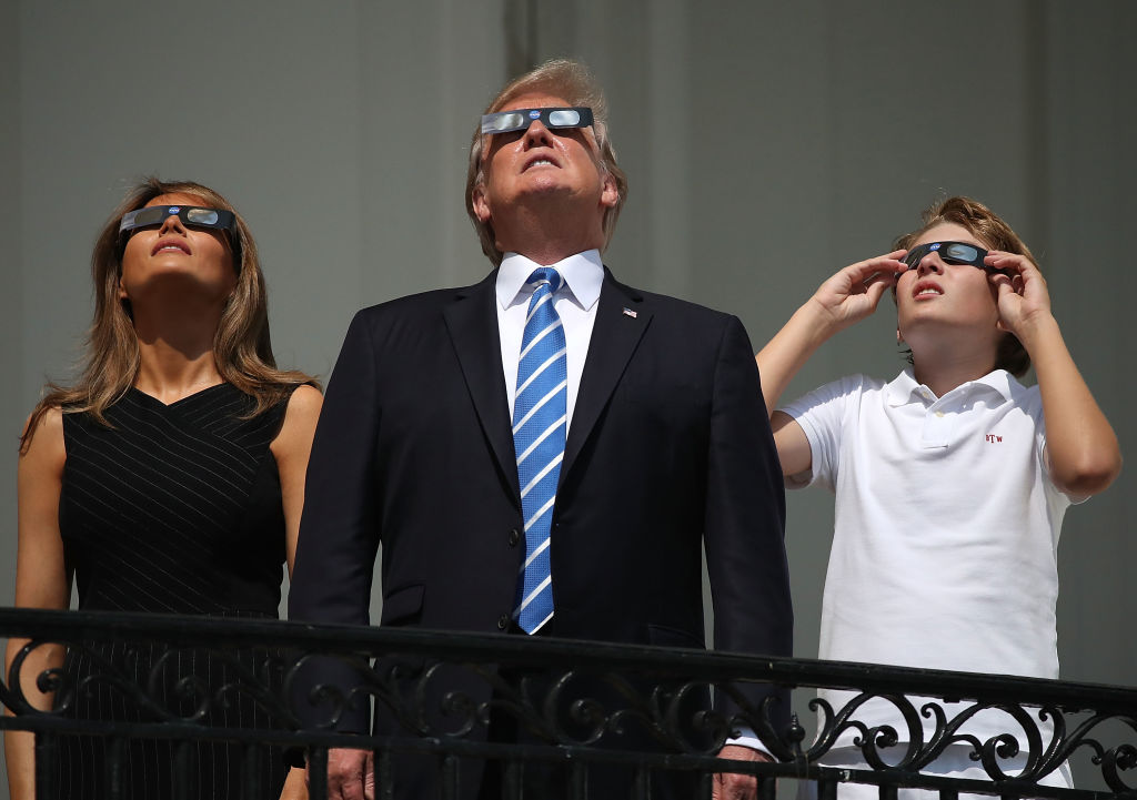 U.S. President Donald Trump, First Lady Melania Trump and their son Barron Trump wear special glasses to view the solar eclipse from the Truman Balcony at the White House on August 21, 2017, in Washington, DC. (Photo by Mark Wilson/Getty Images)