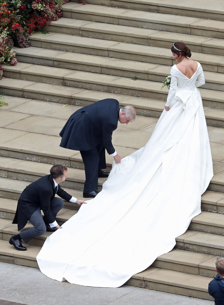 Princess Eugenie of York receives help with her train from her father Prince Andrew, Duke of York as she arrives at her wedding to Mr. Jack Brooksbank at St. George's Chapel on October 12, 2018, in Windsor, England. (Getty Images)