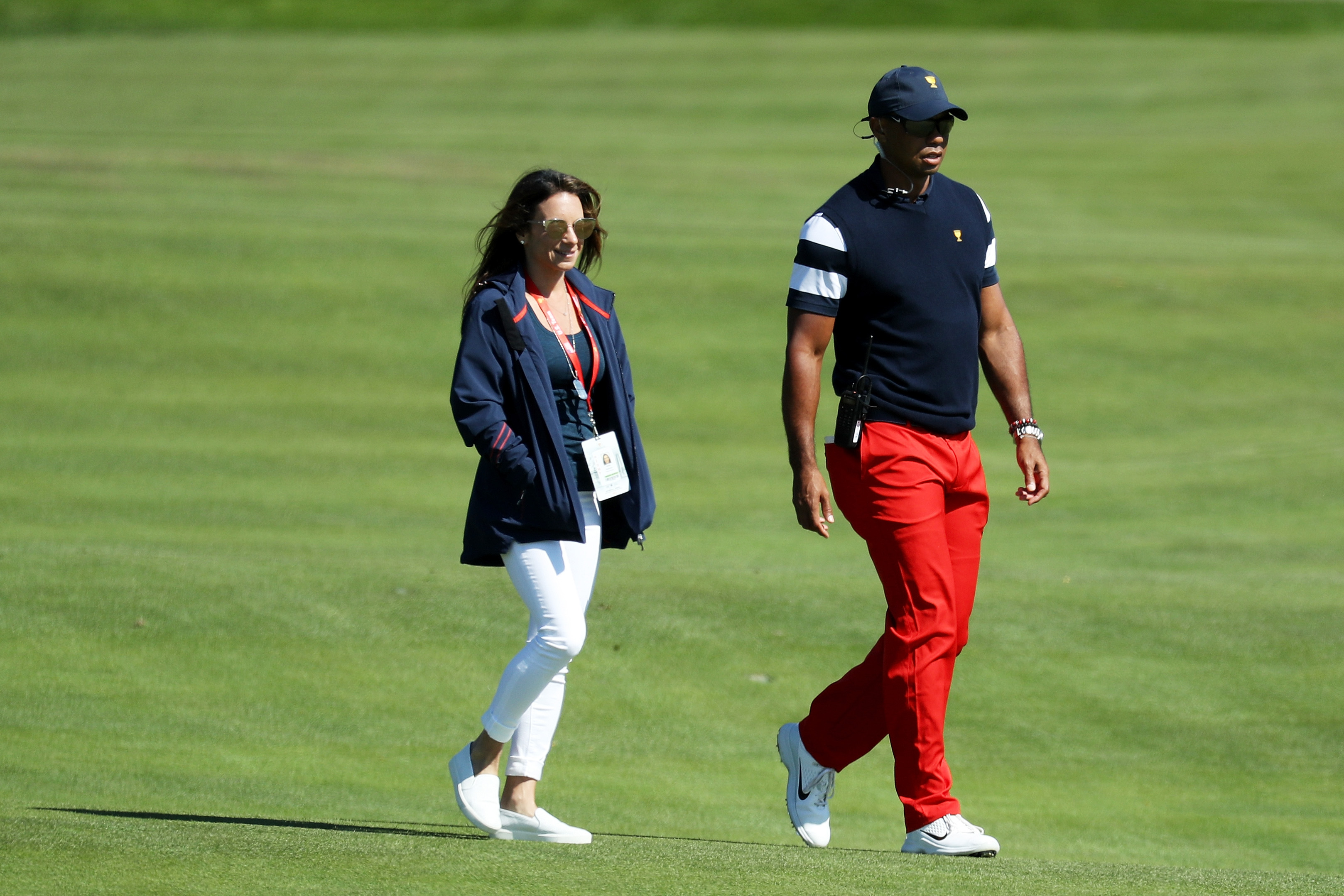 Captain's assistant Tiger Woods of the U.S. Team and Erica Herman walk on the first hole during Sunday singles matches of the Presidents Cup at Liberty National Golf Club on October 1, 2017, in Jersey City, New Jersey. (Getty Images)