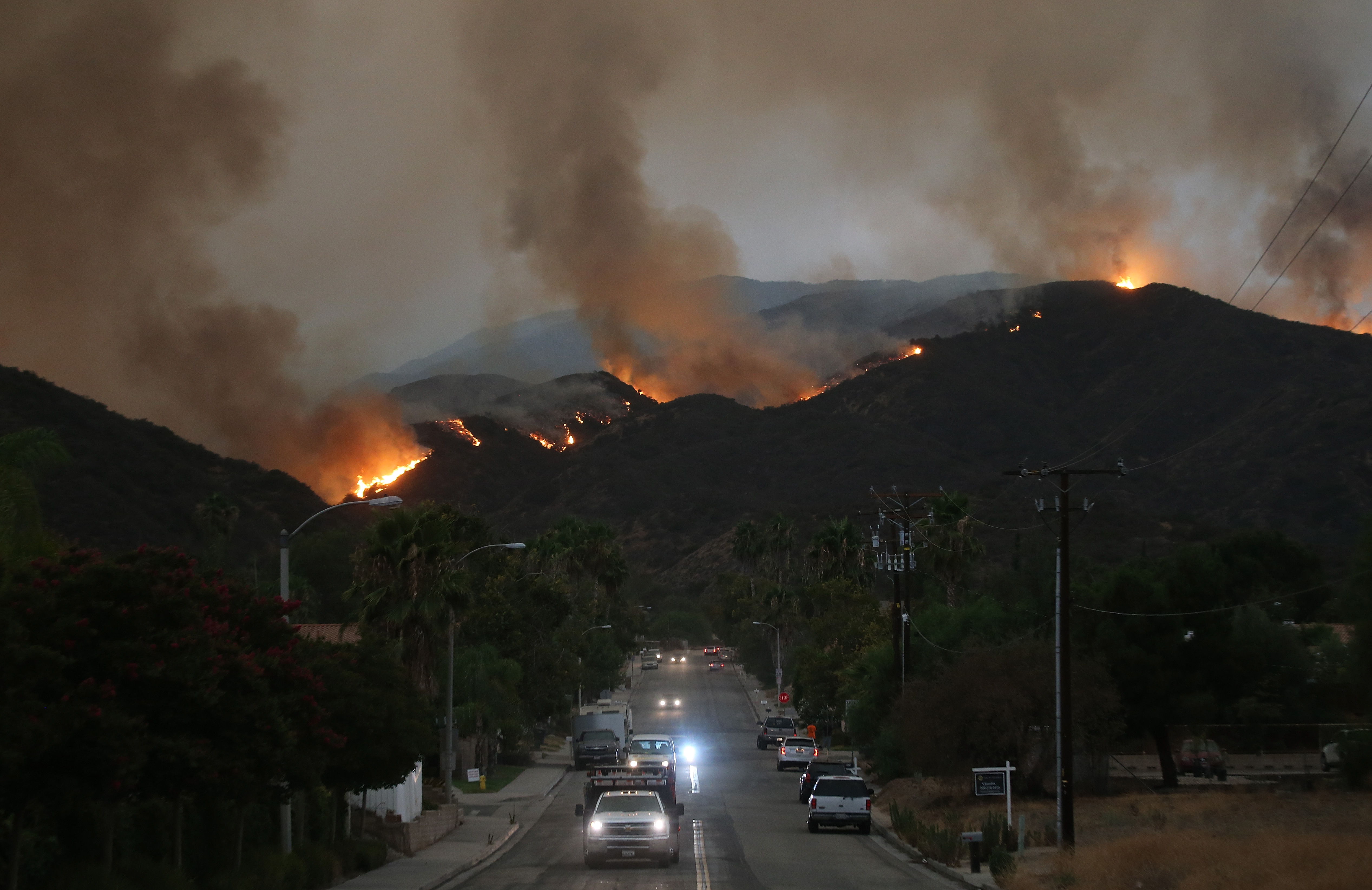 Cars drive down a hill in a mandatory evacuation area as the Holy Fire burns in Cleveland National Forest on August 8, 2018 in Lake Elsinore, California. The fire has burned at least 6,200 acres and destroyed twelve structures.