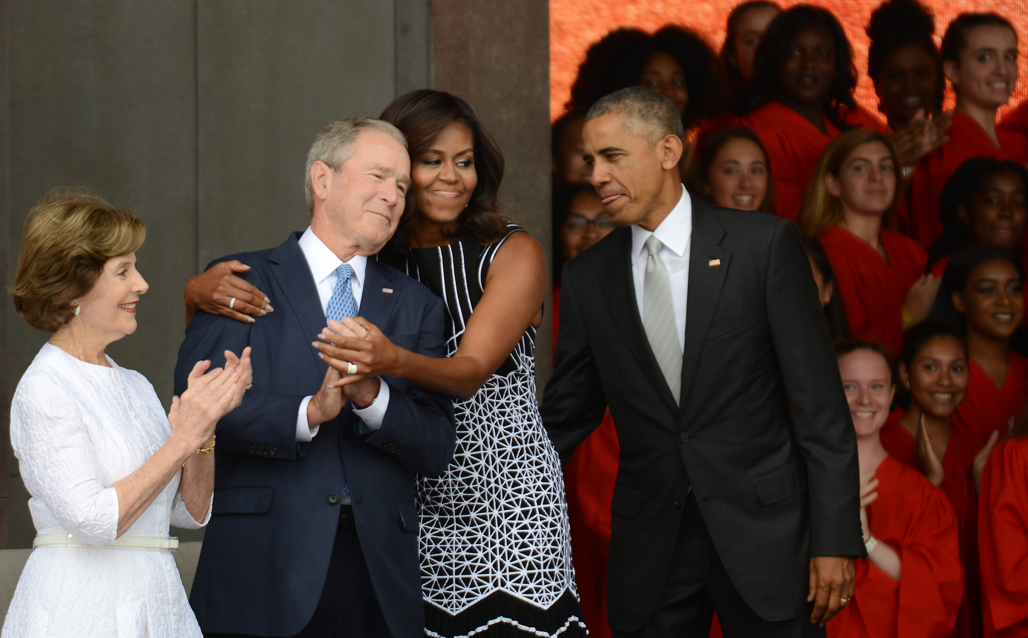 President Barack Obama watches first lady Michelle Obama embracing former president George Bush, accompanied by his wife, former first lady Laura Bush.