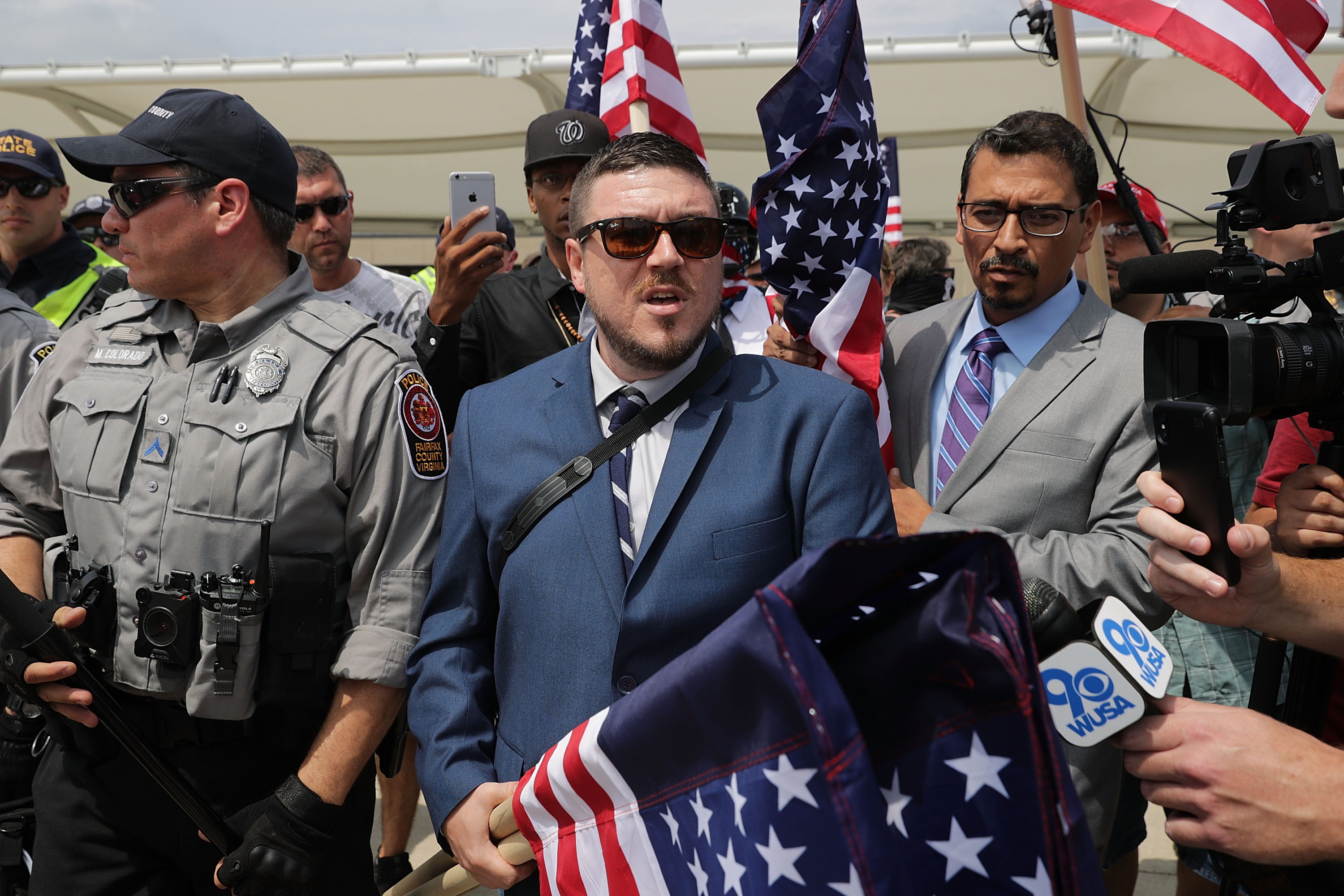 Surrounded by his supporters, reporters and Fairfax County Police, Jason Kessler (C) walks toward the Vienna/Fairfax GMU Metro Station to travel by train to the White House for his white supremacist 'Unite the Right' rally August 12, 2018 in Vienna, Virginia. Thousands of protesters are expected to demonstrate against the 'white civil rights' rally in Washington, which was planned by the organizer of last year's deadly rally in Charlottesville, Virginia.