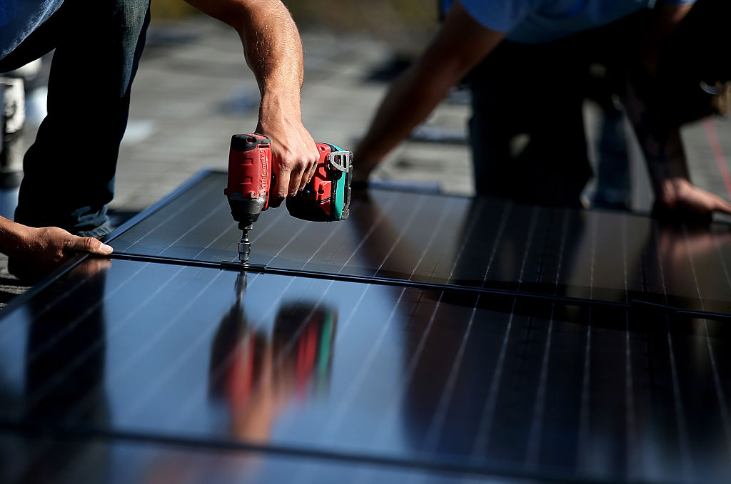 Workers install solar panels on the roof of a home on February 26, 2015, in San Rafael, California (Source: Getty Images)