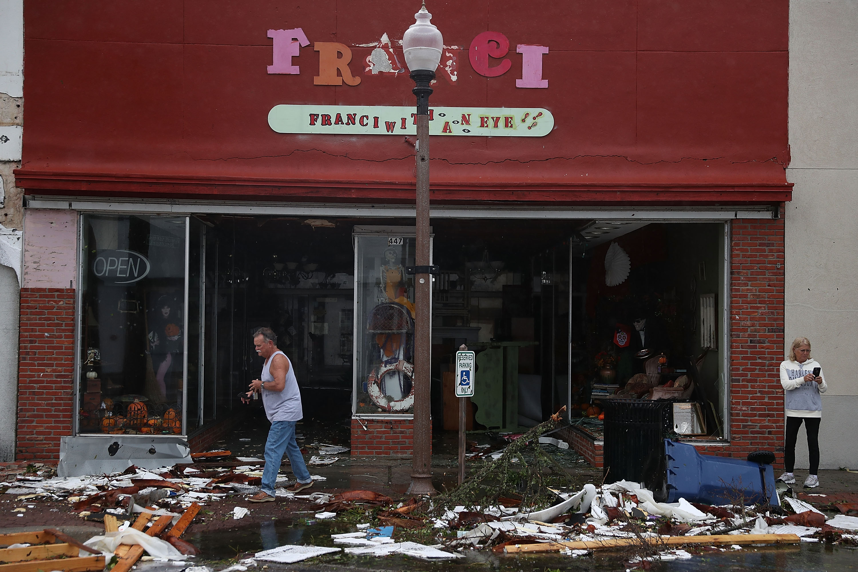 People walk past damaged stores after hurricane Michael passed through the downtown area on October 10, 2018 in Panama City, Florida. The hurricane hit the Florida Panhandle as a category 4 storm.