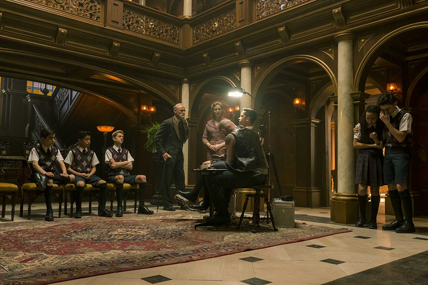 Sir Reginald Hargreeves giving the children tattoos of the family's insignia, in 'The Umbrella Academy'. (Source: IMDB)