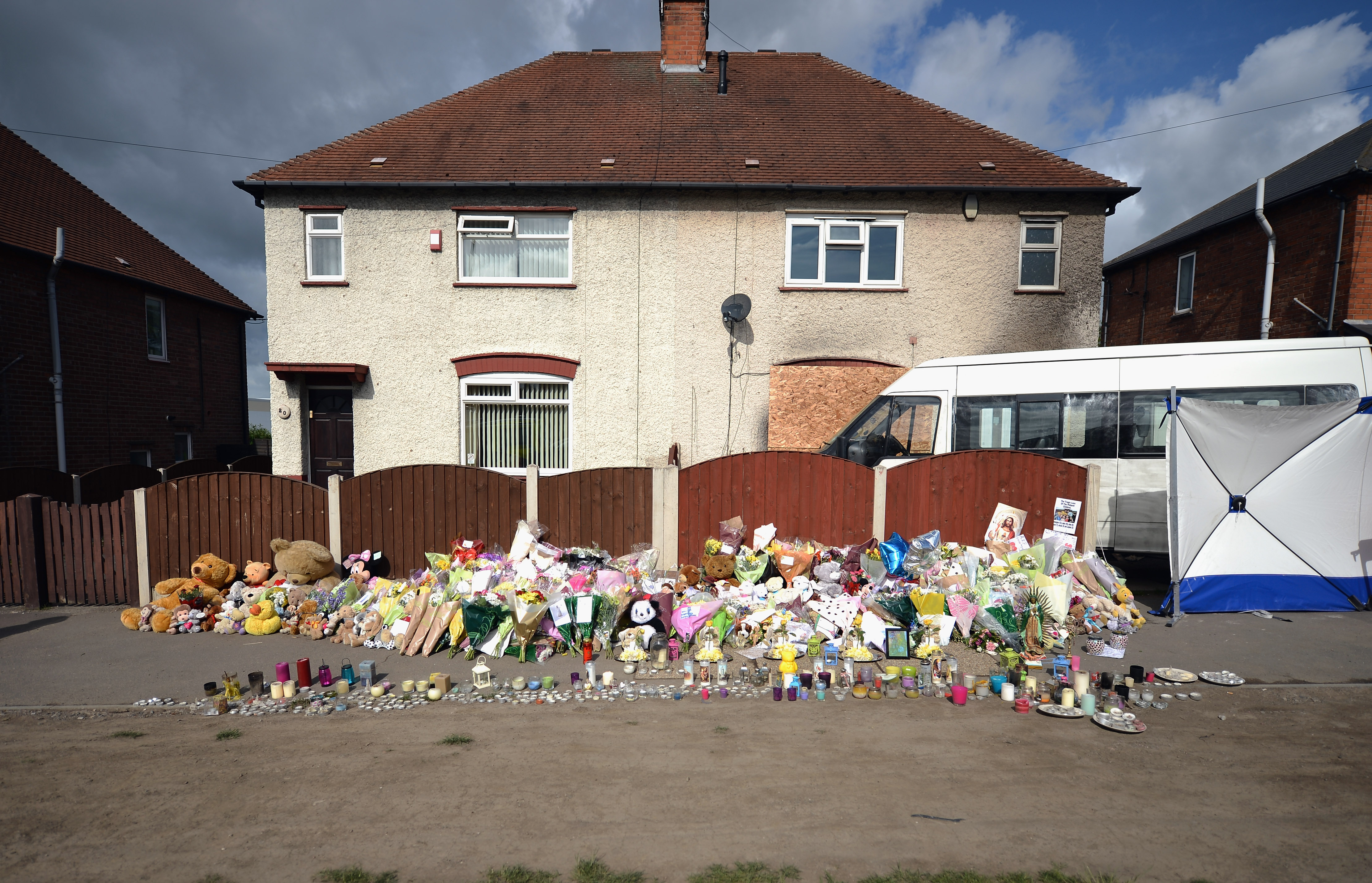 The family home with tributes for the children lining the pavement outside (Source: Christopher Furlong/Getty Images)