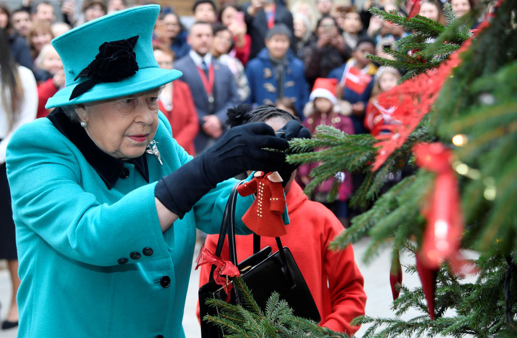 Queen Elizabeth II and Shylah Gordon, aged 8, attach a bauble to a Christmas tree during the opening of the Queen Elizabeth II centre at CORAM on December 05, 2018, in London, England. (Getty Images)