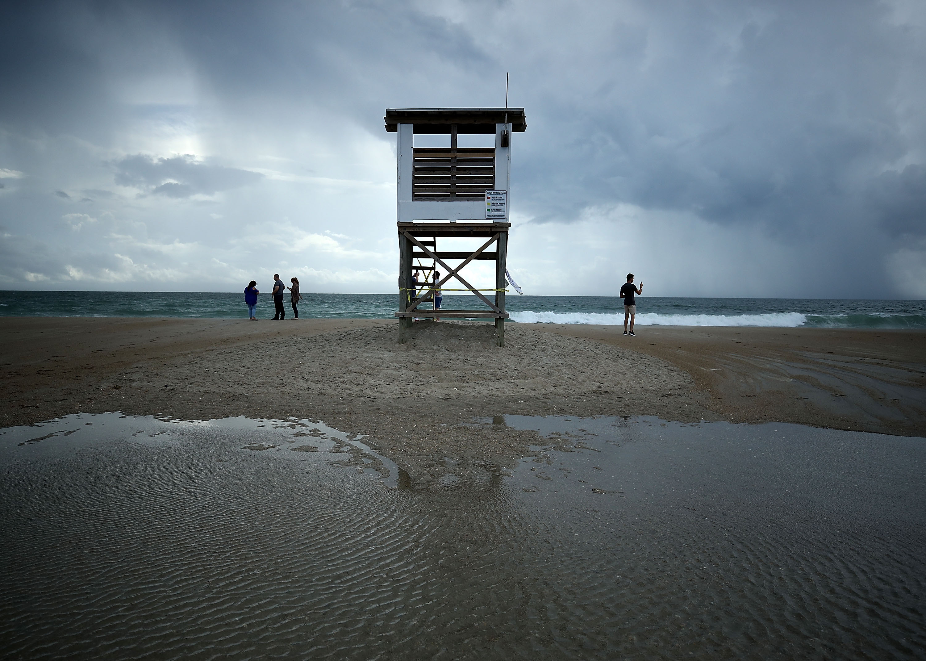 People stand near a lifeguard stand as Hurricane Florence approaches, on September 11, 2018 in Wrightsville Beach, United States. Hurricane Florence is expected on Friday possibly as a category 4 storm along the Virginia, North Carolina and South Carolina coastline.