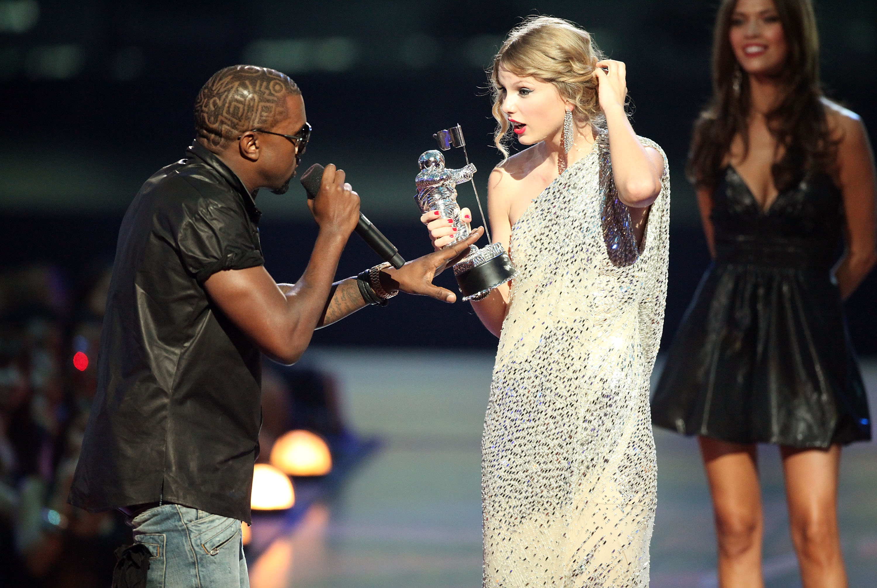 Kanye West (L) jumps onstage after Taylor Swift (C) won the 'Best Female Video' award during the 2009 MTV Video Music Awards at Radio City Music Hall on September 13, 2009 in New York City.
