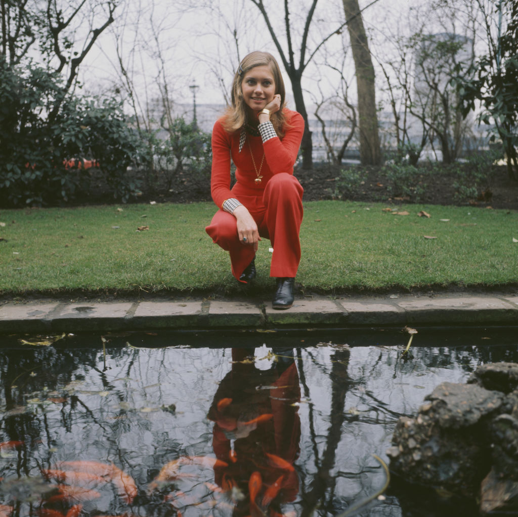 English-Australian singer, Olivia Newton-John, by a goldfish pond outside the Savoy Hotel in London, circa 1970. (Photo by Keystone/Hulton Archive/Getty Images)