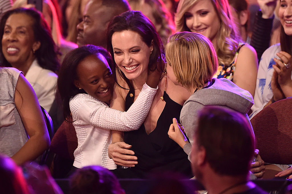 Angelina Jolie hugs Zahara Marley Jolie-Pitt (L) and Shiloh Nouvel Jolie-Pitt (R) at The Forum on March 28, 2015 in Inglewood, California. (Photo by Kevin Winter/Getty Images)