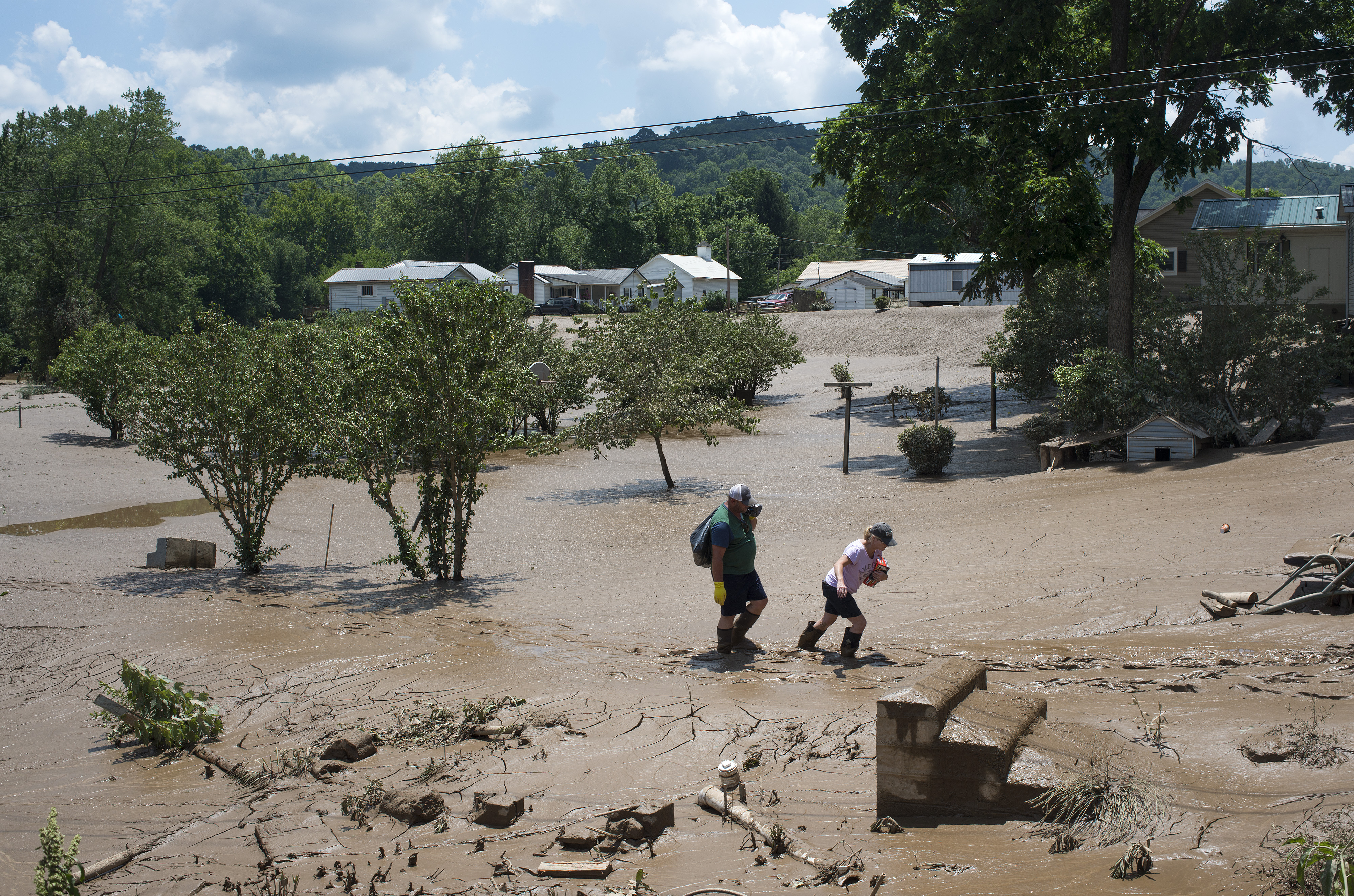 People trudge through the mud left over from the flooding of the Elk River along State Route 119, on June 25, 2016, in Falling Rock, West Virginia. The flooding of the Elk River claimed the lives of at least 23 people in West Virginia. (Getty Images)