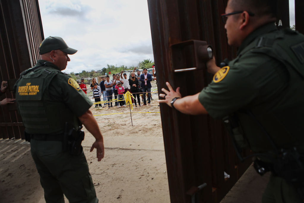 U.S. Border Patrol agents close the border gate, as people look on from the Mexican side of the border, at the conclusion of the Hugs Not Walls event on the U.S.-Mexico border on October 13, 2018, in Sunland Park, New Mexico. (Photo by Mario Tama/Getty Images)