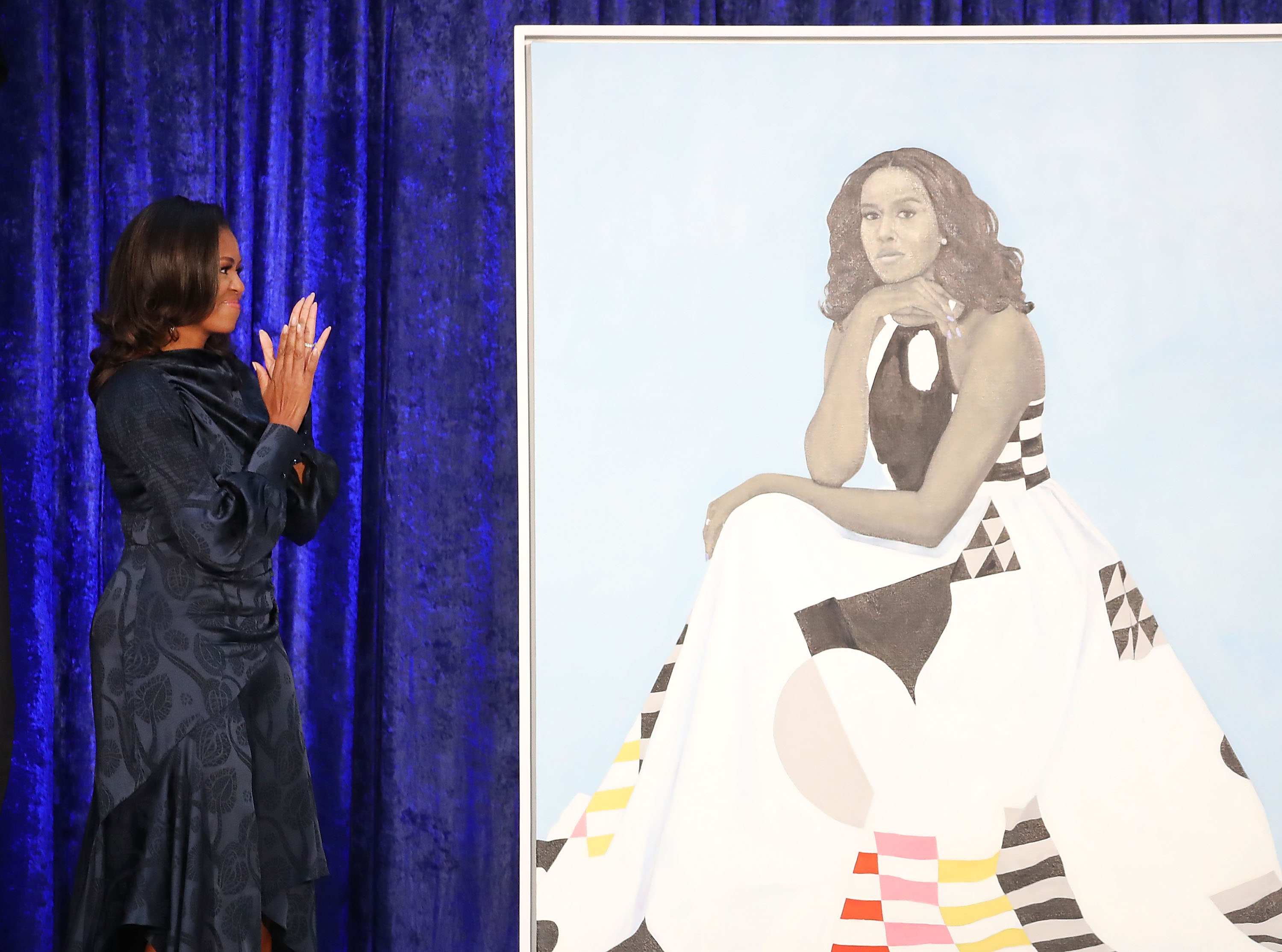 Former US first lady Michelle Obama looks at her newly unveiled portrait during a ceremony at the Smithsonian's National Portrait Gallery, on February 12, 2018 in Washington, DC. The portraits were commissioned by the Gallery, for Kehinde Wiley to create President Obama's portrait, and Amy Sherald that of Michelle Obama.