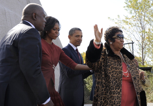 Aretha Franklin (R) accepts applause as she finishes her performance with U.S. President Barack Obama, first lady Michelle Obama and Harry Johnson, president and CEO of the MLK National Memorial Project Fund (L) as they attend the dedication of the Martin Luther King, Jr Memorial on the National Mall October 16, 2011 in Washington, DC. The ceremony for the slain civil rights leader had been postponed earlier in the summer because of Hurricane Irene. (Photo by Mike Theiler-Pool/Getty Images)