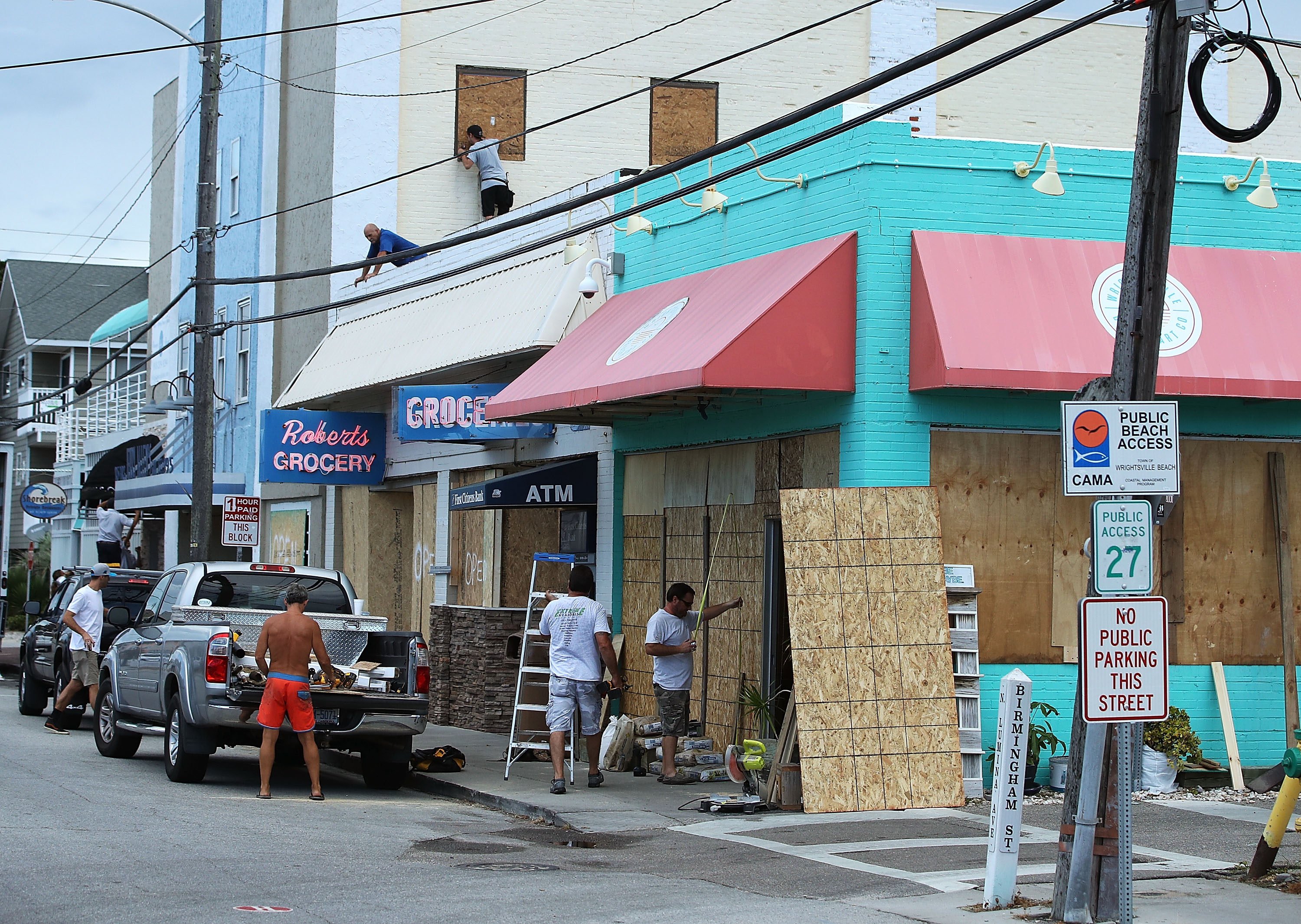 Workers board up shops while preparing for the arrival of Hurricane Florence on September 11, 2018 in Wrightsville Beach, United States. Hurricane Florence is expected on Friday possibly as a category 4 storm along the Virginia, North Carolina and South Carolina coastline.