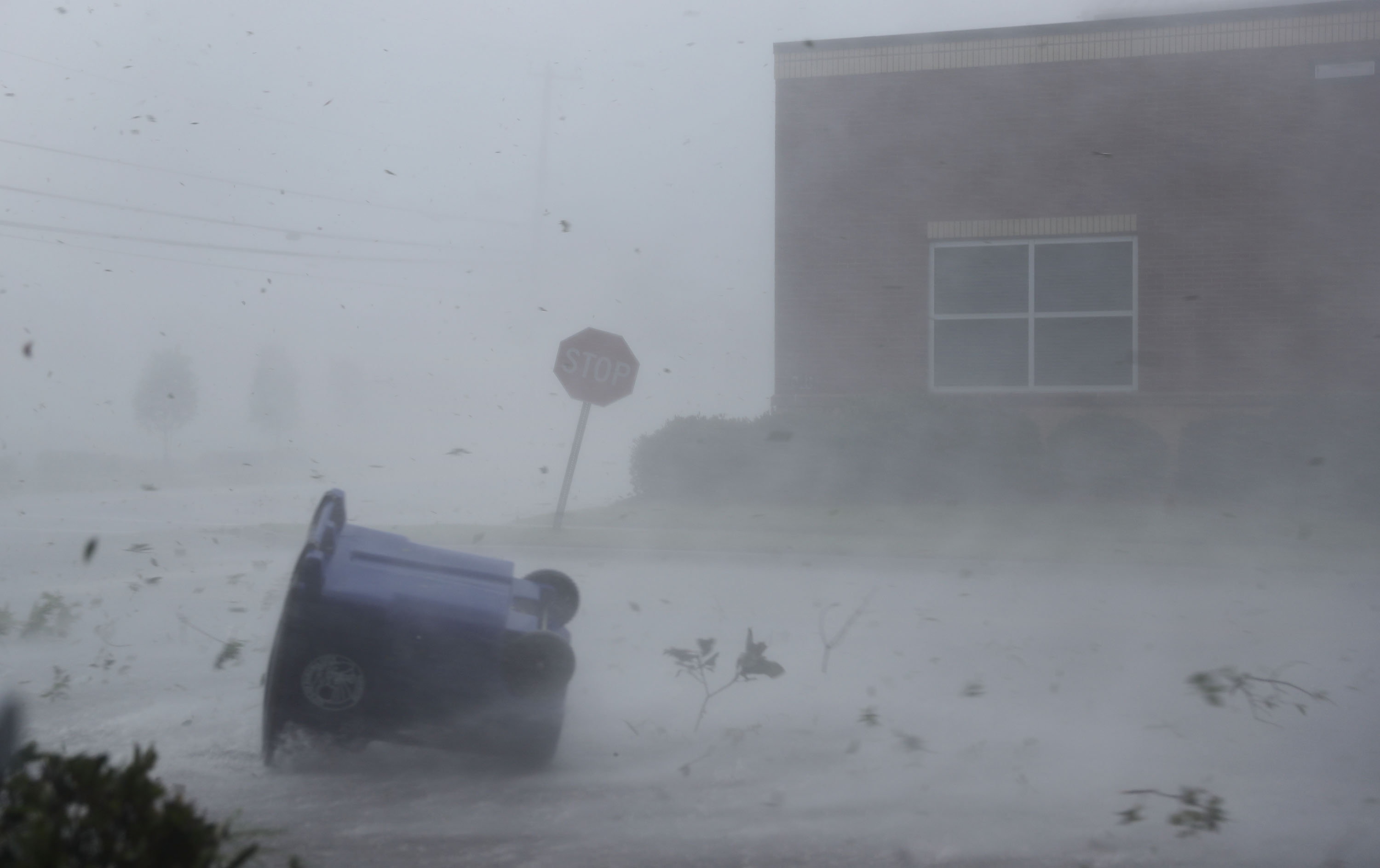 A trash can and debris are blown down a street by Hurricane Michael on October 10, 2018 in Panama City, Florida. The hurricane made landfall on the Florida Panhandle as a category 4 storm.