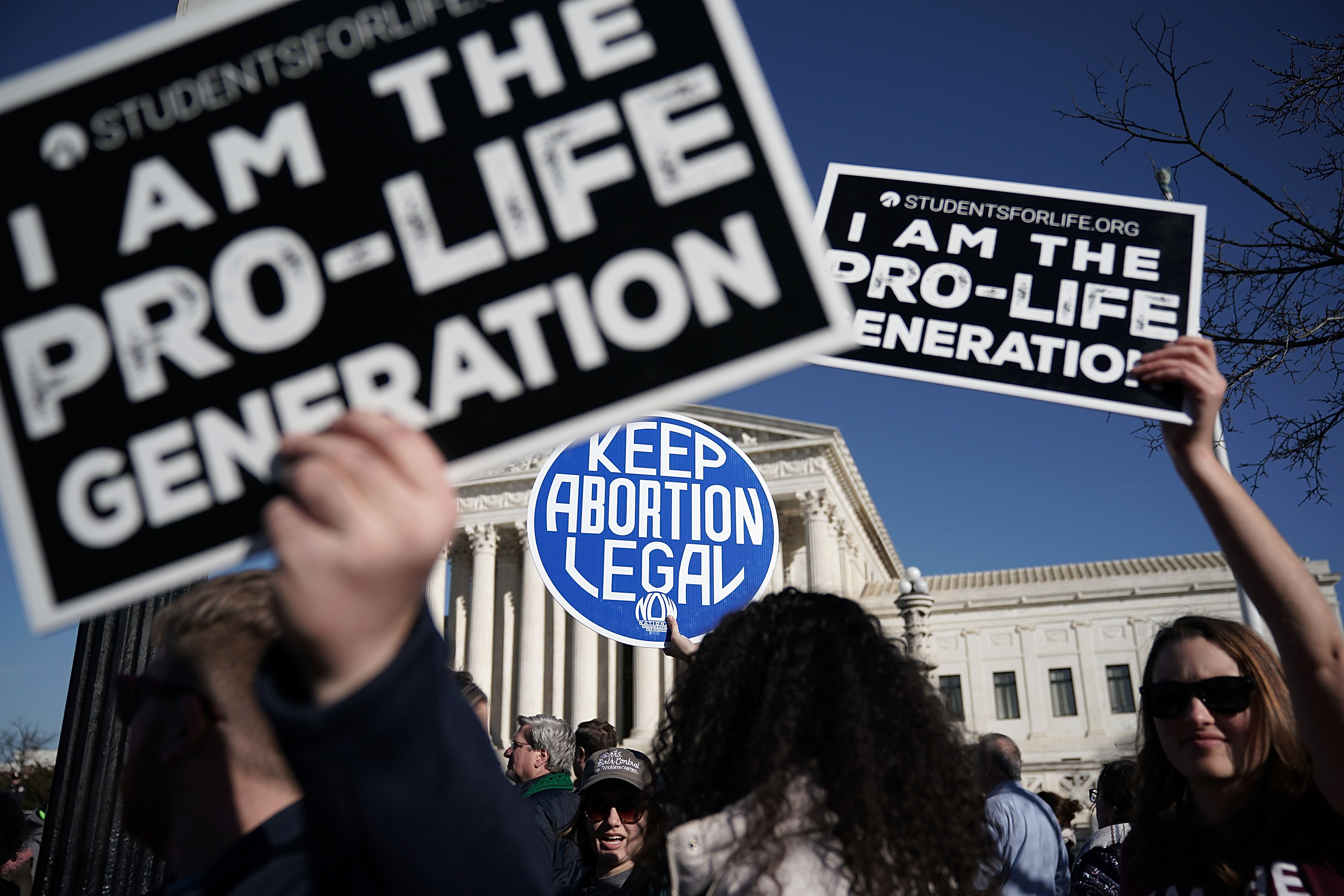 Pro-life activists try to block the sign of a pro-choice activist during the 2018 March for Life January 19, 2018 in Washington, DC. Activists gathered in the nation's capital for the annual event to protest the anniversary of the Supreme Court Roe v. Wade ruling that legalized abortion in 1973. (Getty Images)