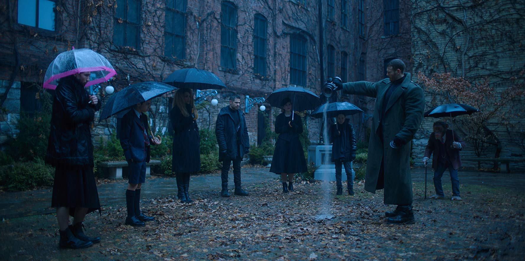 The Umbrella Academy standing in front of what seems to be Ben Hargreeves memorial statue. (2019) Source: IMDB