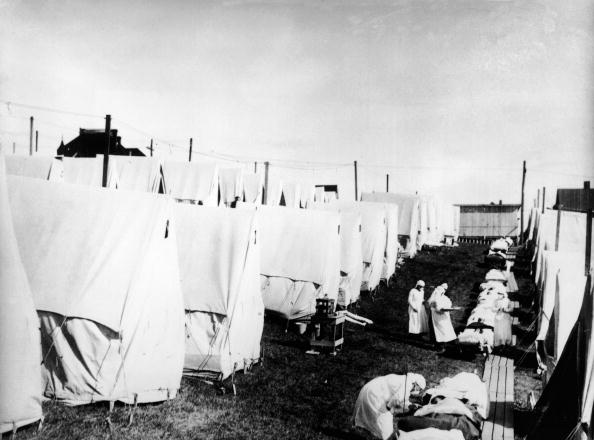Masked doctors and nurses treat flu patients lying on cots and in outdoor tents at a hospital camp during the influenza epidemic of 1918 (Getty Images)