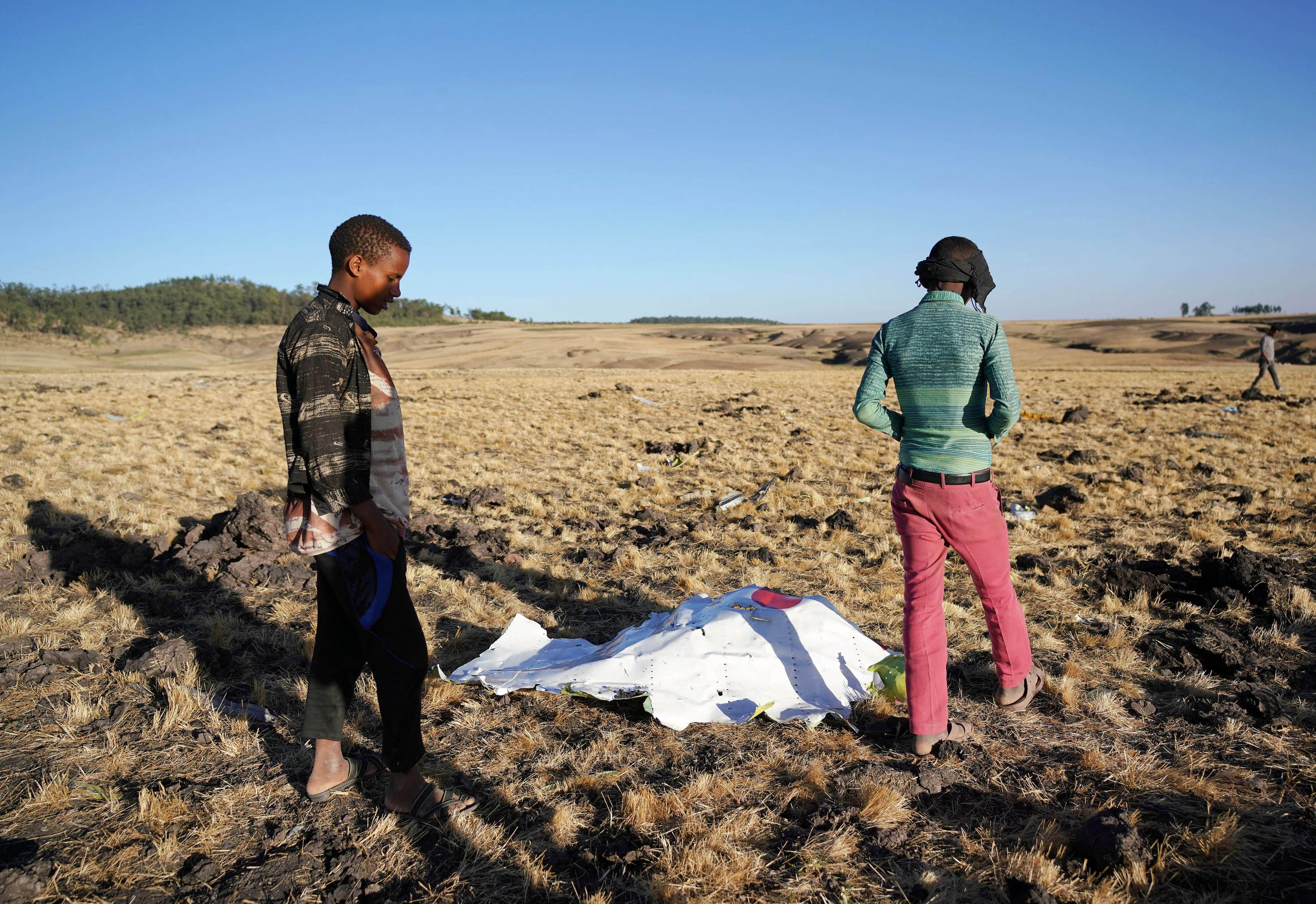 Local residents look at debris at the scene where Ethiopian Airlines Flight 302 crashed in a wheat field just outside the town of Bishoftu, 62 kilometers southeast of Addis Ababa on March 10, 2019, in Addis Ababa, Ethiopia. (Getty)