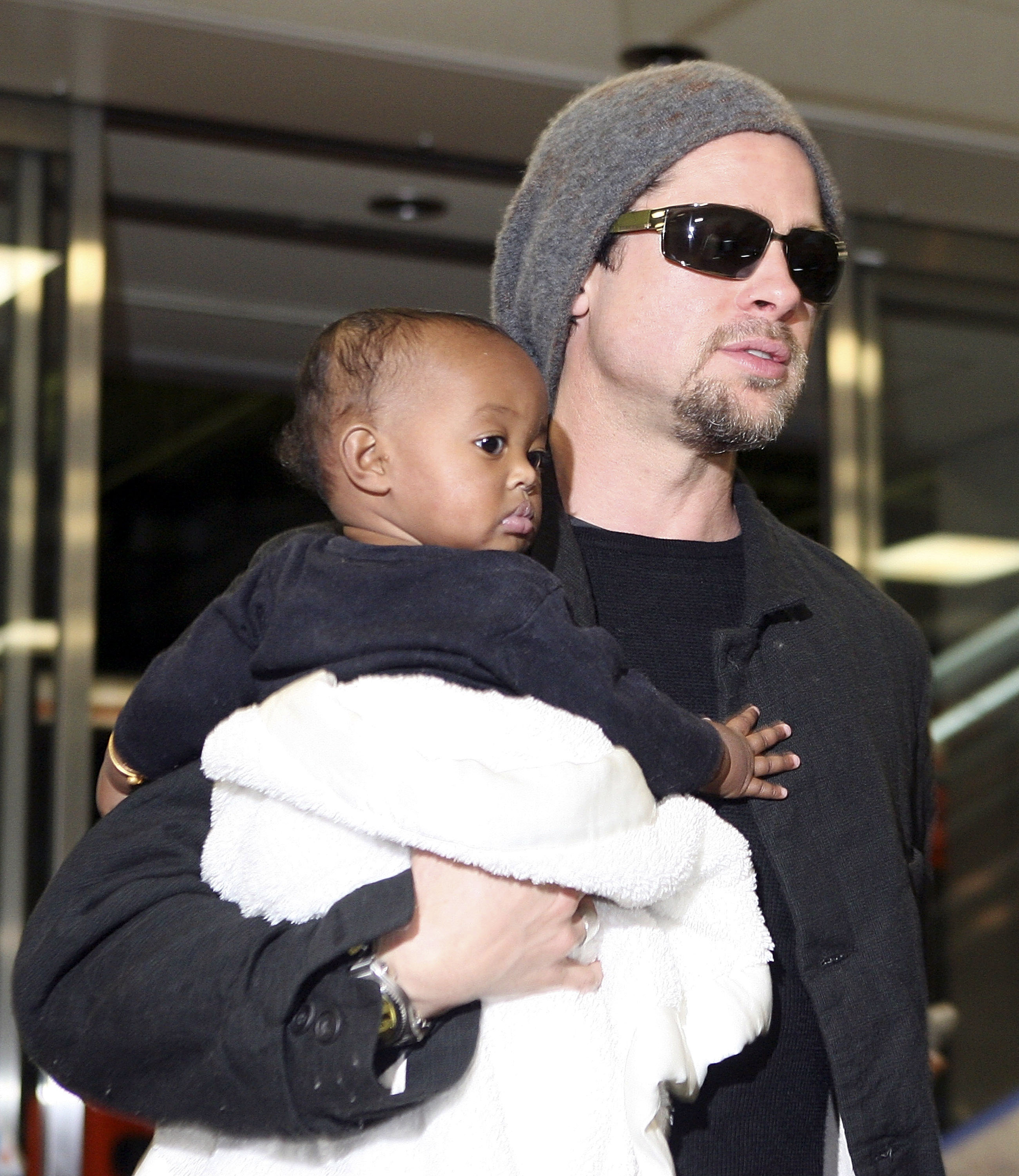 Actor Brad Pitt holds Zahara Marley Jolie (Angelina Jolie's daughter) as they arrive at the New Tokyo International Airport on November 27, 2005 in Narita, Japan. Pitt and Angelina Jolie are in Japan to promote a film 'Mr. and Mrs. Smith.' (Photo by Koichi Kamoshida/Getty Images)