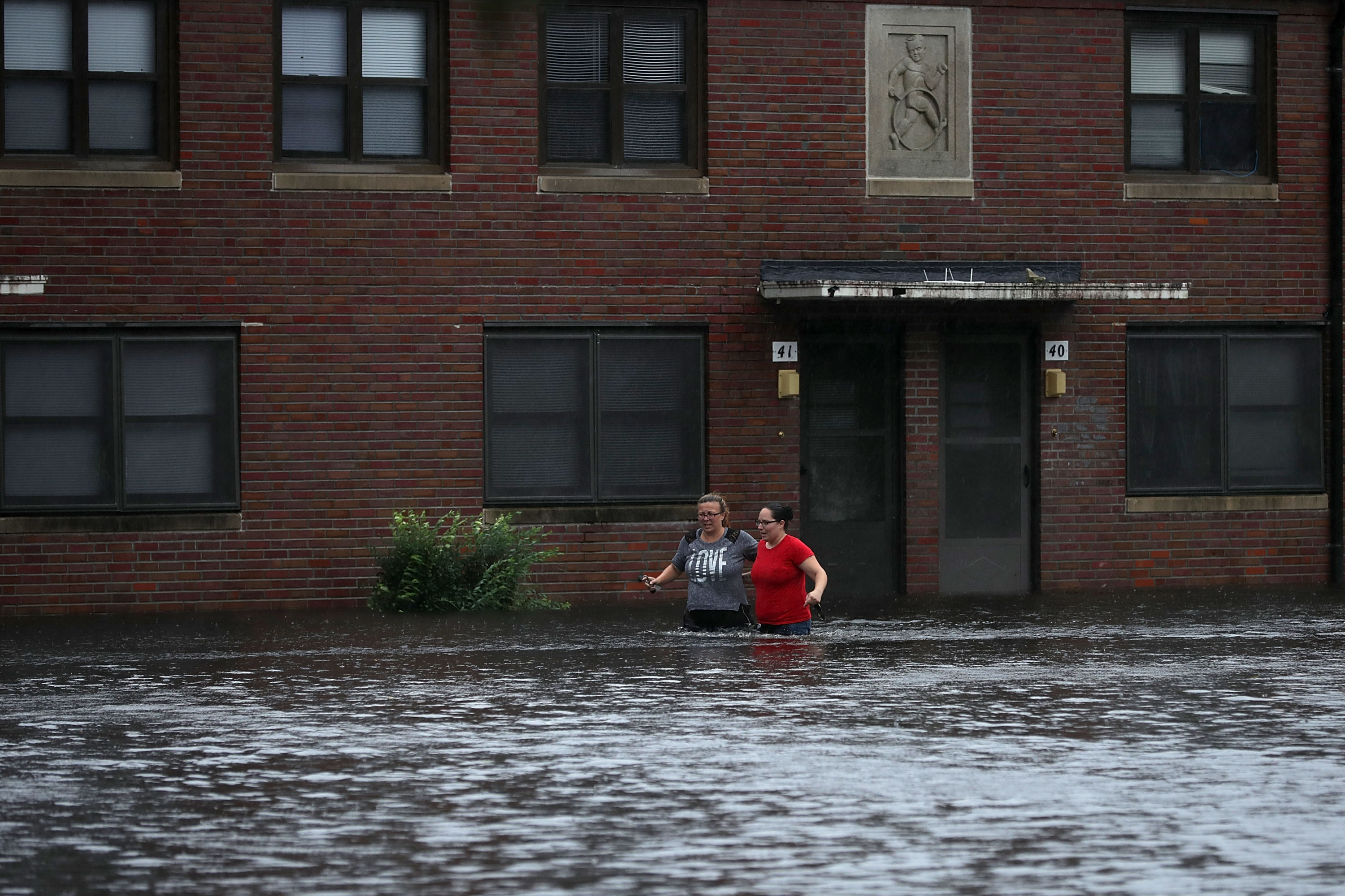 Residents wade through deep floodwater to retrieve belongings from the Trent Court public housing apartments after the Neuse River went over its banks during Hurricane Florence September 13, 2018 in New Bern, United States. Coastal cities in North Carolina, South Carolina and Virginia are under evacuation orders as the Category 2 hurricane approaches the United States.