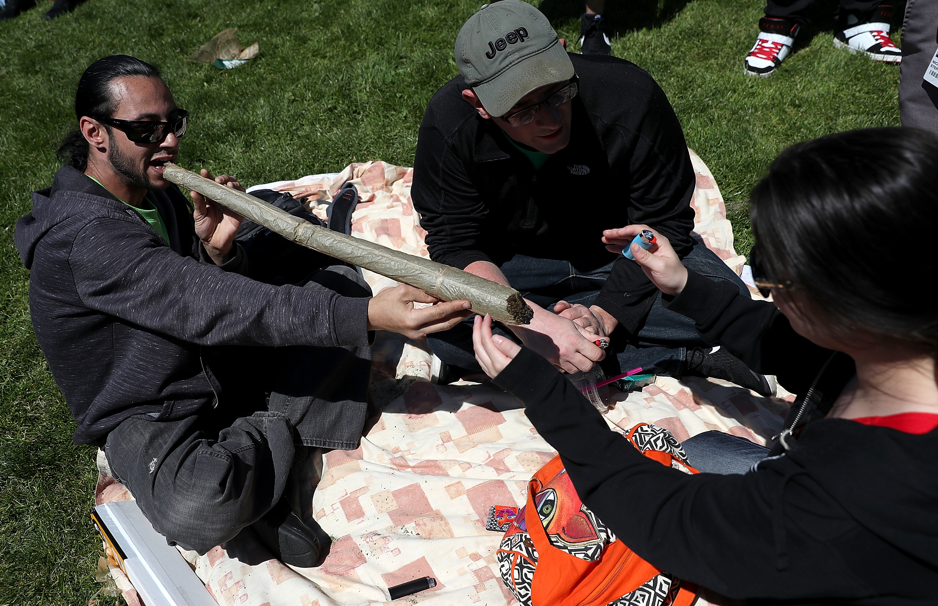 A marijuana user attempts to light an oversized joint during a 420 Day celebration on 'Hippie Hill' in Golden Gate Park on April 20, 2018, in San Francisco, California. (Getty)