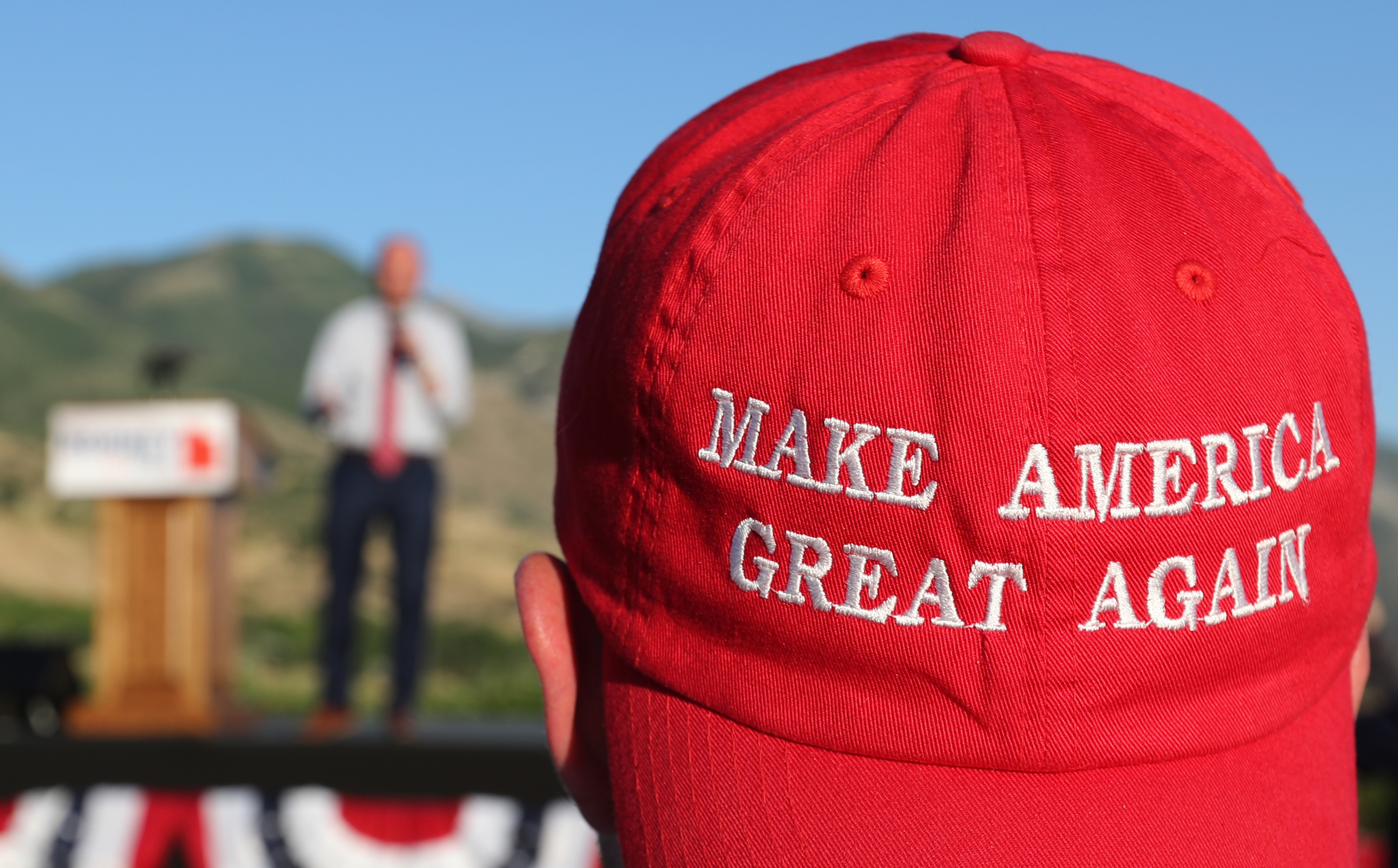 A Romney supporter listens to a speaker as he wears a 'Make America Great Again' hat at the Mitt Romney election party on June 26, 2018 in Orem, Utah (Getty Images)