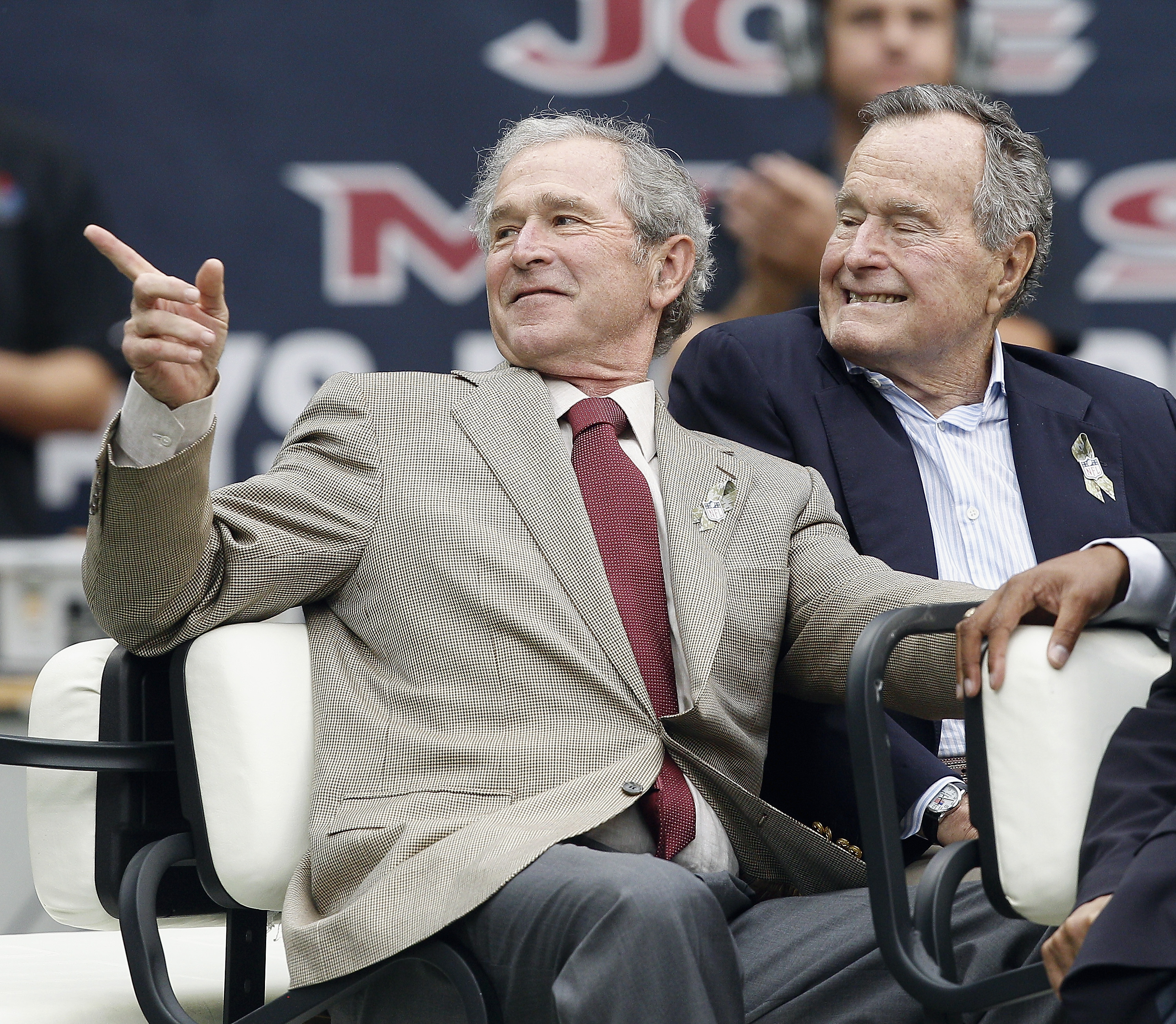Former Presidents George W. Bush (L) and George H.W. Bush attend a game between the Oakland Raiders and Houston Texans at Reliant Stadium on November 17, 2013 in Houston, Texas.