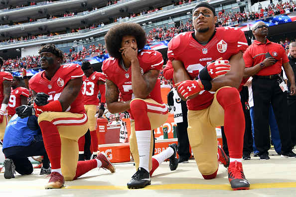 Eli Harold #58, Colin Kaepernick #7 and Eric Reid #35 of the San Francisco 49ers kneel on the sideline during the anthem prior to the game against the Dallas Cowboys at Levi's Stadium. (Getty Images)