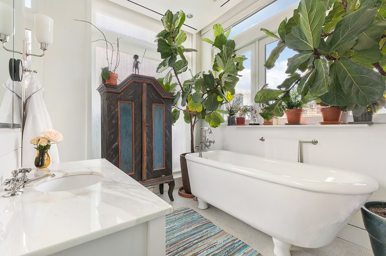 The en-suite master bath is outfitted with a marble-topped vanity, a deep soaking tub and a number of tropical plants for effect and ambiance. (Donna Dotan)