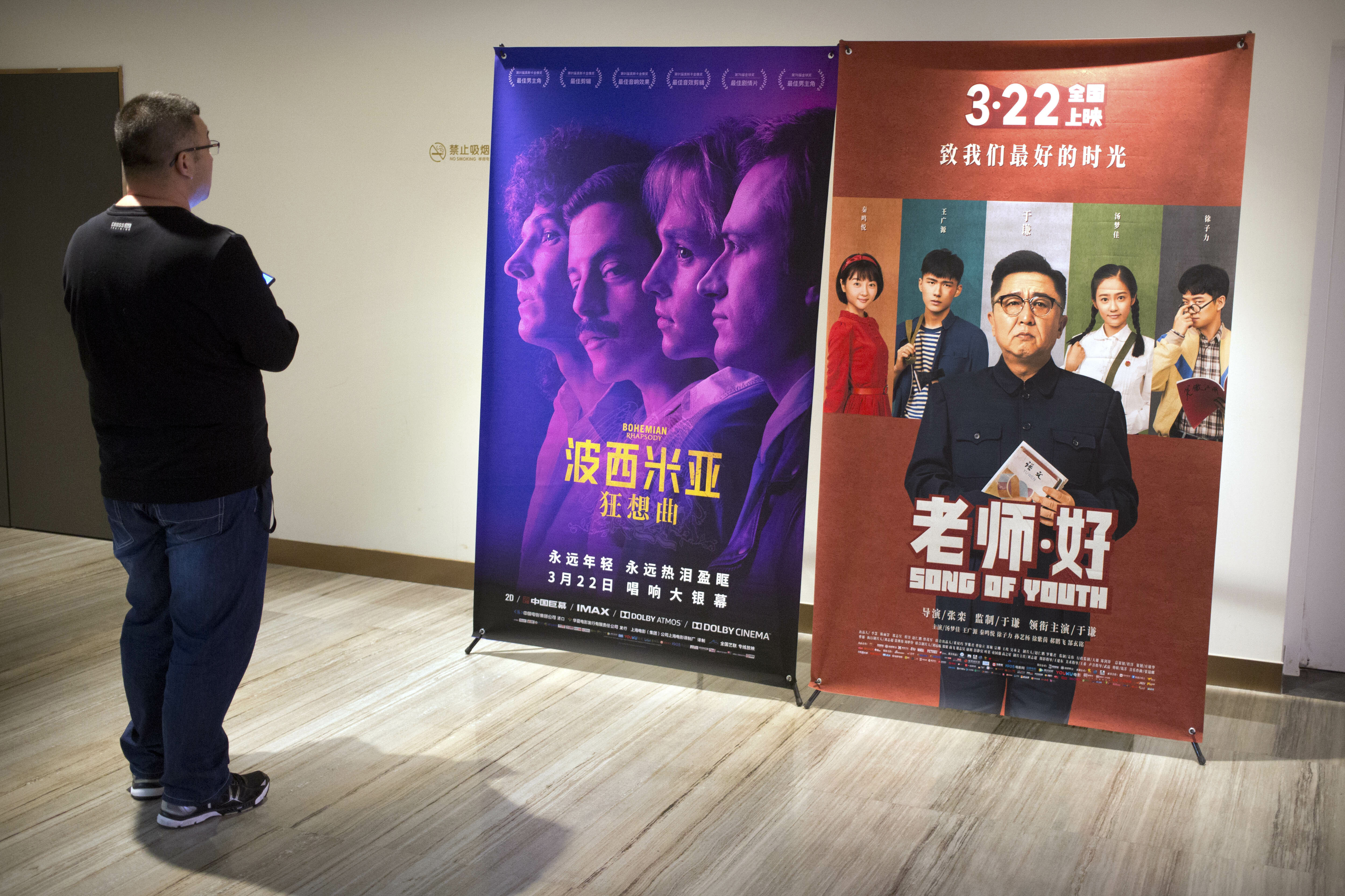 "A customer looks at a movie poster for the film ""Bohemian Rhapsody"" at a movie theater in Beijing, Wednesday, March 27, 2019. Moviegoers in China say the version of the ""Bohemian Rhapsody"" shown in Chinese theaters erases mentions of Freddie Mercury's sexuality. The biopic on the lead singer of the British rock band Queen omitted a same-sex kiss and lacked scenes in which Mercury reveals he's not straight and has AIDS. (AP Photo/Mark Schiefelbein)"