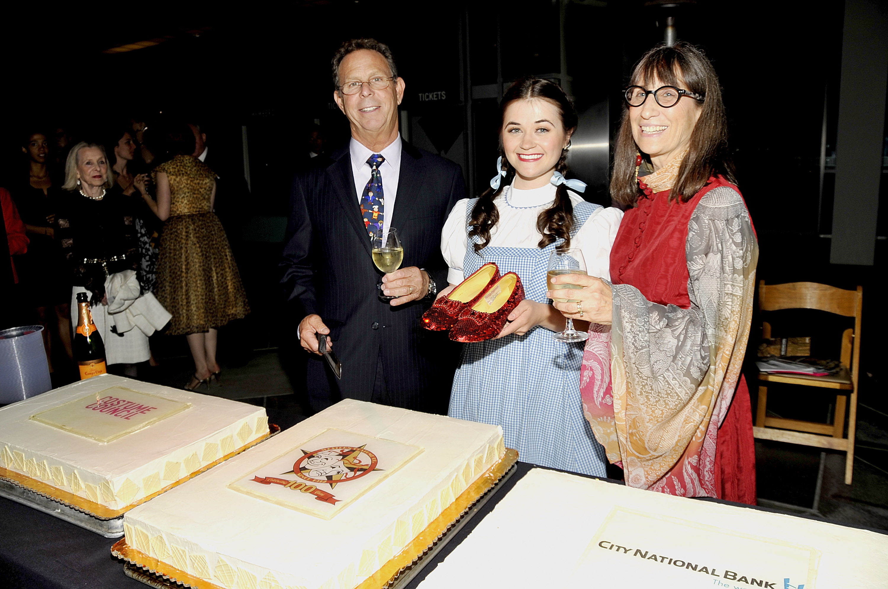 (L-R) President of Western Costume Company, Eddie Marks, the model wearing the Dorthy dress and holding thr ruby red sippers that were worn by Judy Garland in 'The Wizard Of Oz' and head of research at Western Costum Company Bobi Garland prepare to cut the cake at The Costume Council Of LACMA Celebrates The Western Costume Company: The First 100 Years at the Bing Theatre At LACMA on June 20, 2012 in Los Angeles, California.
